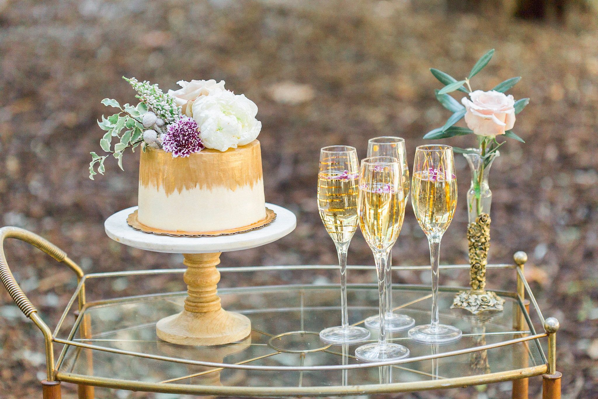 White frosted buttercream cake, painted gold and topped with a floral arrangement. Photo:  Yasmin Roohi