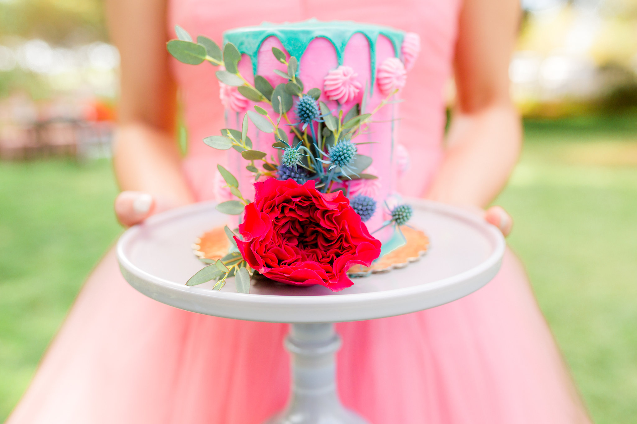Pink frosted cake with teal chocolate drip, buttercream accents and flowers. Photo:  Yasmin Roohi