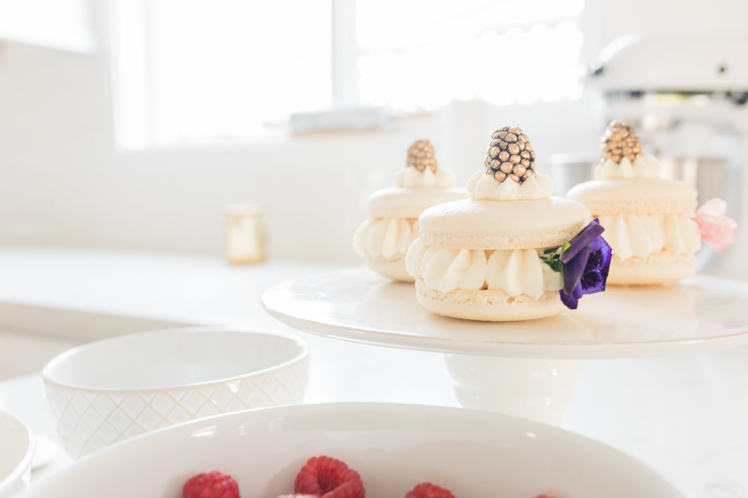 Large Macaron Sandwiches with gold dusted berries and edible flowers. Photo:  Yasmin Roohi