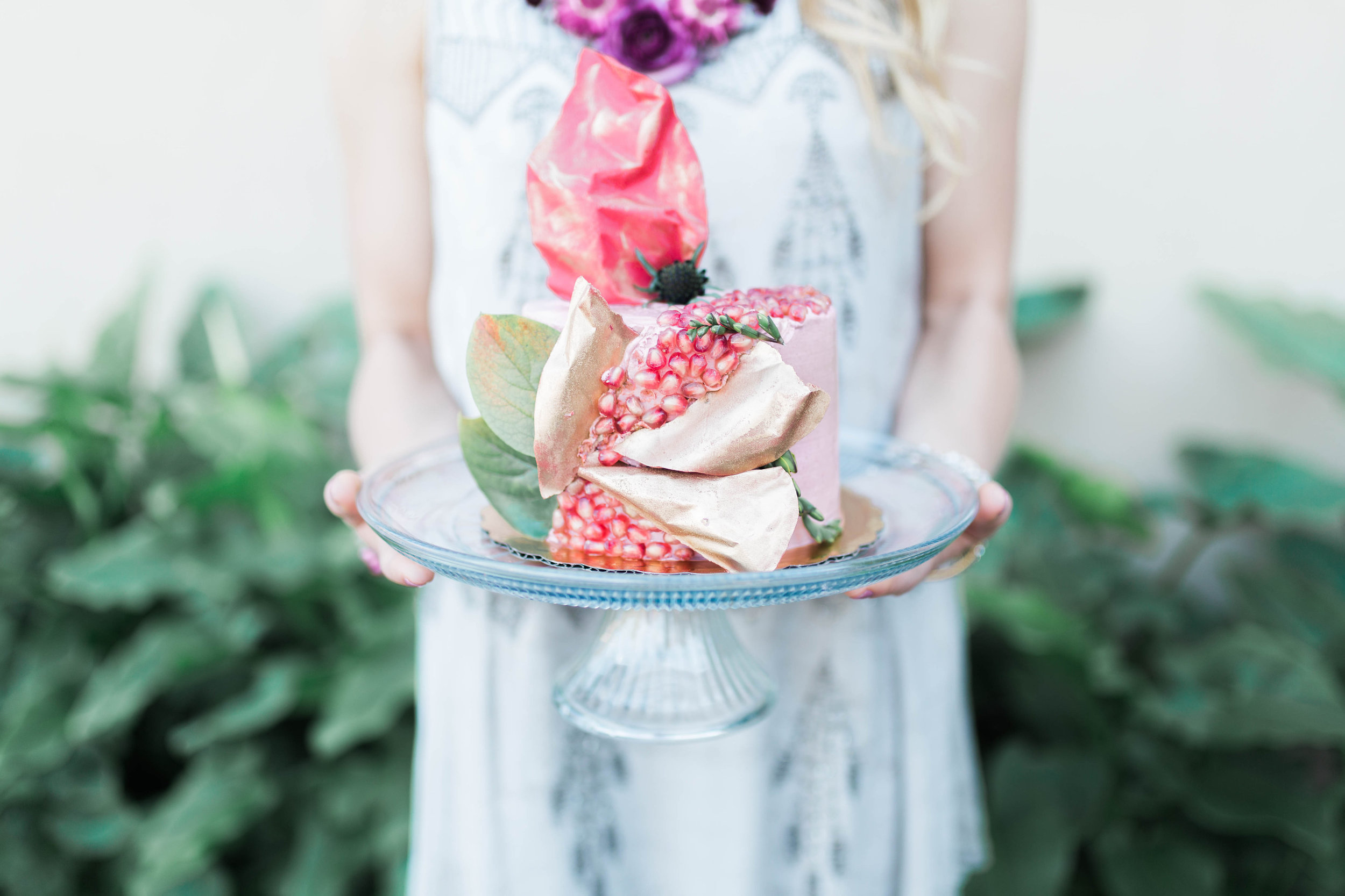 Frosted cake decorated with pomegranate seeds and gold chocolate shards. Photo: Amanda Azarpour