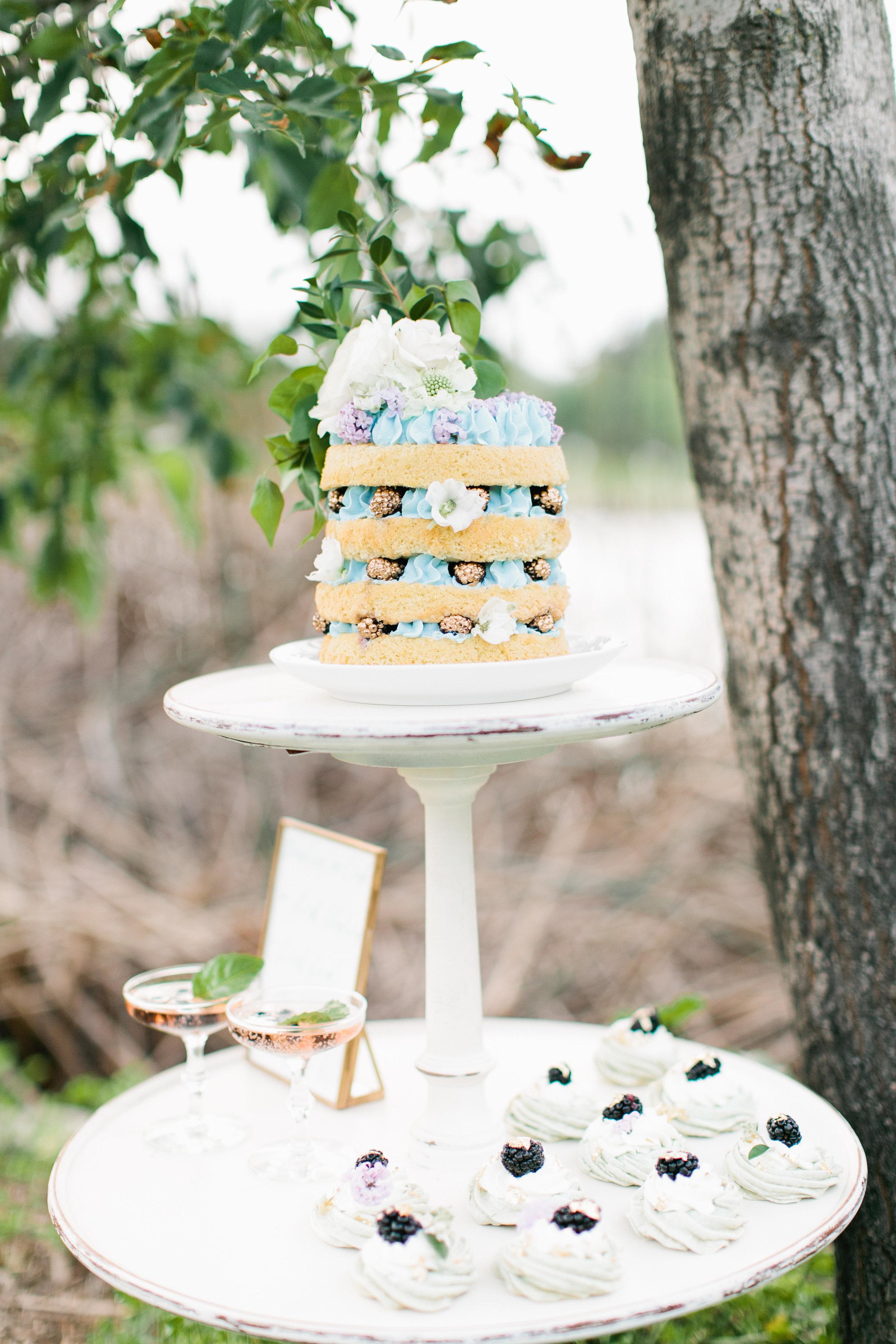 Naked sponge cake with bright blue buttercream, gold blackberries, fresh florals. Photo: Sorella Muse