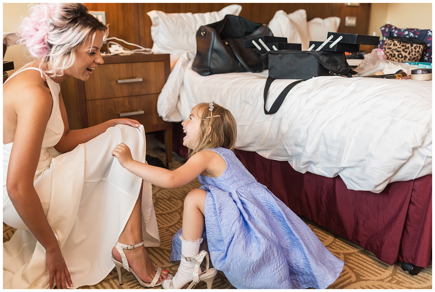 Bridesmaids and flower girl helping bride into dress | Kingston wedding
