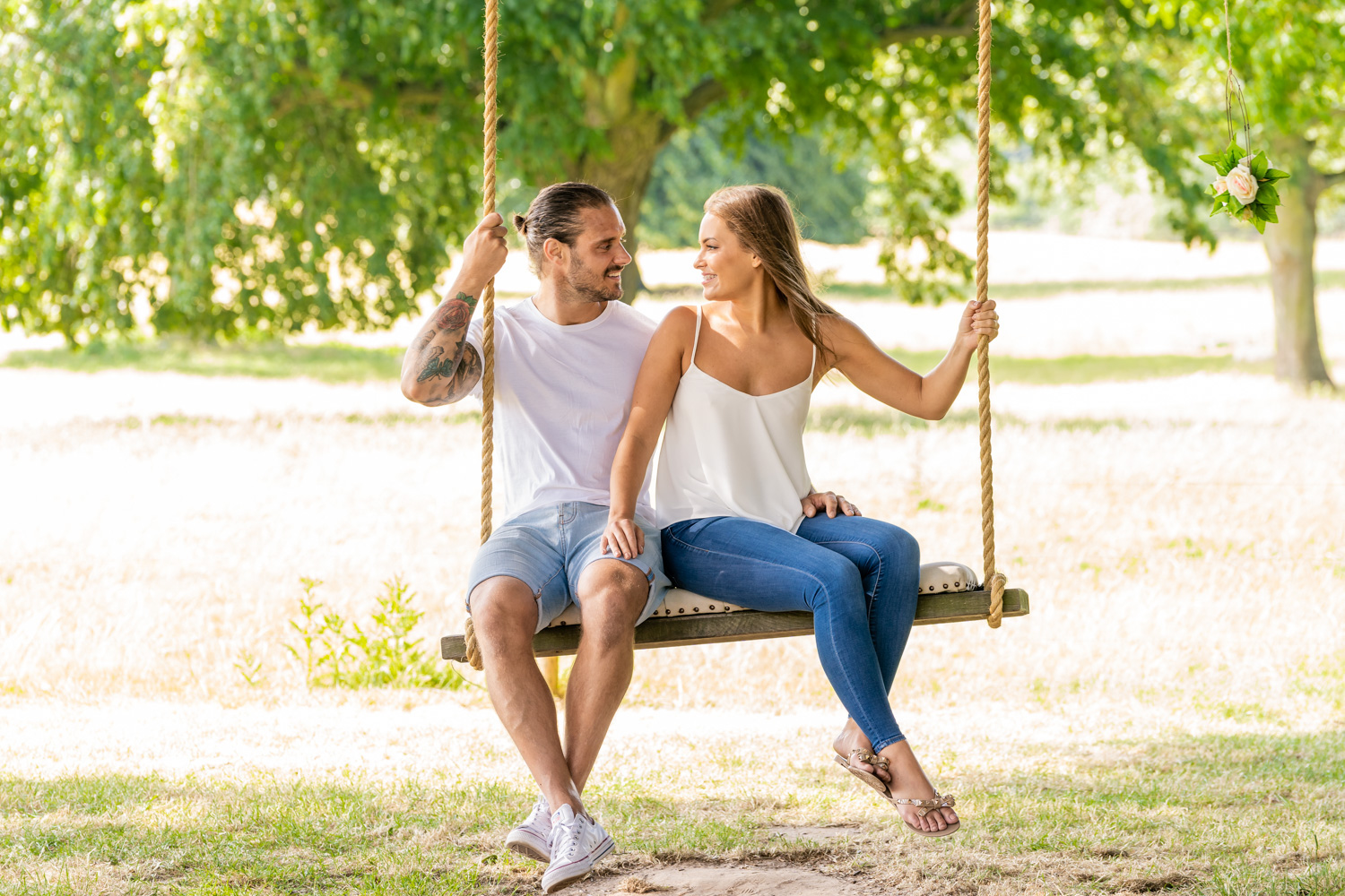 Pre wed couple having fun and enjoying their engagement shoot as the play around on a swing in a Surrey park