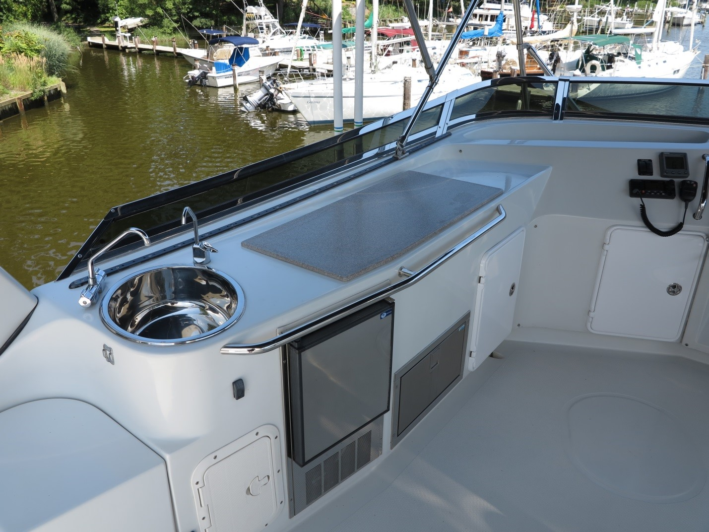 The updated flybridge area includes a Corian countertop, Seagull filtered water faucet, and access door to the inside of this large space. If the bridge was fully enclosed, this area could further configured for living on the flybridge. Without the grill, there is space above the fridge for a larger pull-out drawer to hold the many things we need for cruising, entertaining, and simply living aboard.