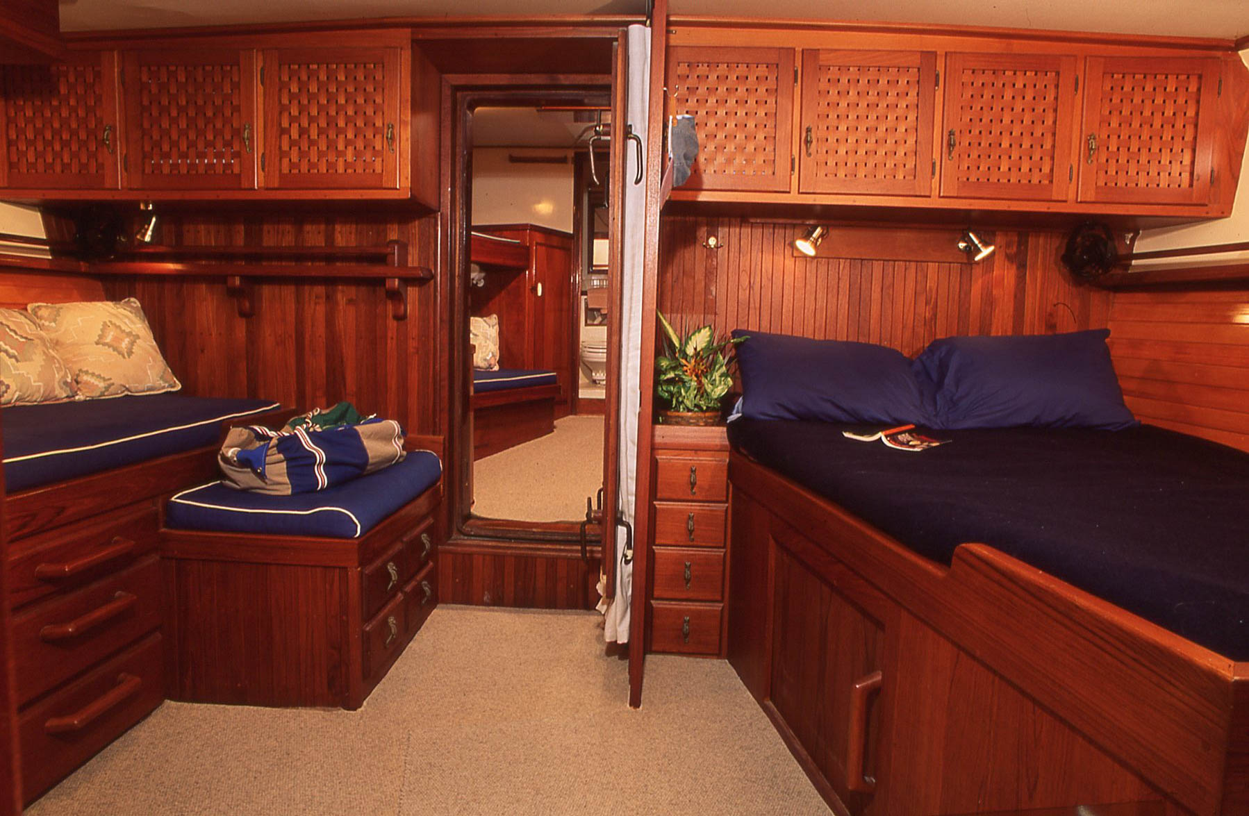 A master stateroom that works well offshore. Making the bed might be more tedious than an island berth arrangement, but it works. Note the separation between the berths in this cabin and the guest stateroom closer to the bow, with guest head beyond.