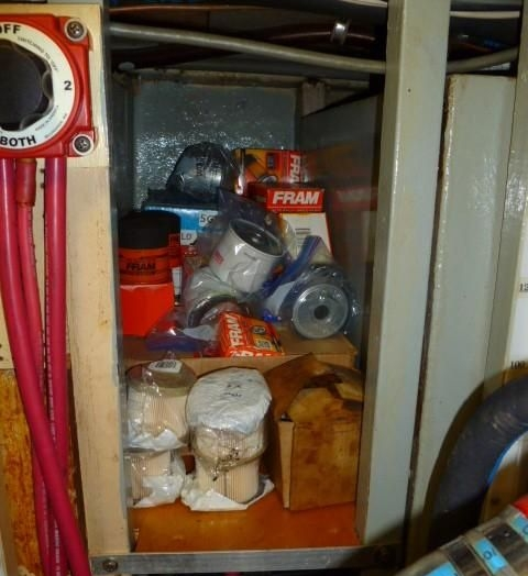 Spare parts and filters and belts get stowed in available space, in this case loose on a shelf. How long before they fall into the bilge when the boat takes a large wake or wave? The sound of things crashing out of lockers and shelves only adds to the anxiety of rough seas.