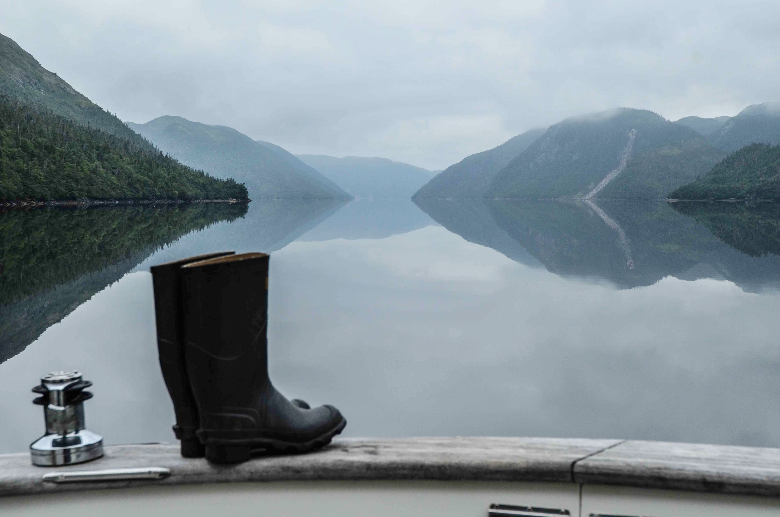 Typical early morning scene in Newfoundland's fjords. It is usually overcast in the mornings with light or sometime heavy fog. By mid-morning the fog lifts exposing the mountains. Mary's boots were waiting for her. We wore wellies like these for all inland exploring inside the fjords. In addition to exploring ashore we also did quite a bit of shoreline dinghy exploring. We even caught two near-shore lobster for dinner from the dink with a dip net.