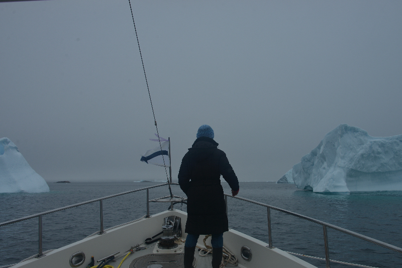 Mary on the foredeck of  Egret  standing ice watch in the fog while passing through Prince Christian Sound, Greenland. She isn't looking for the berg ice you see in the photograph, but tell-tale ripples of black ice floating just at the surface. Black ice is much denser than typical glacier ice or tabular ice and a real bummer to hit under way. It is the difference between hitting wood or cast iron.