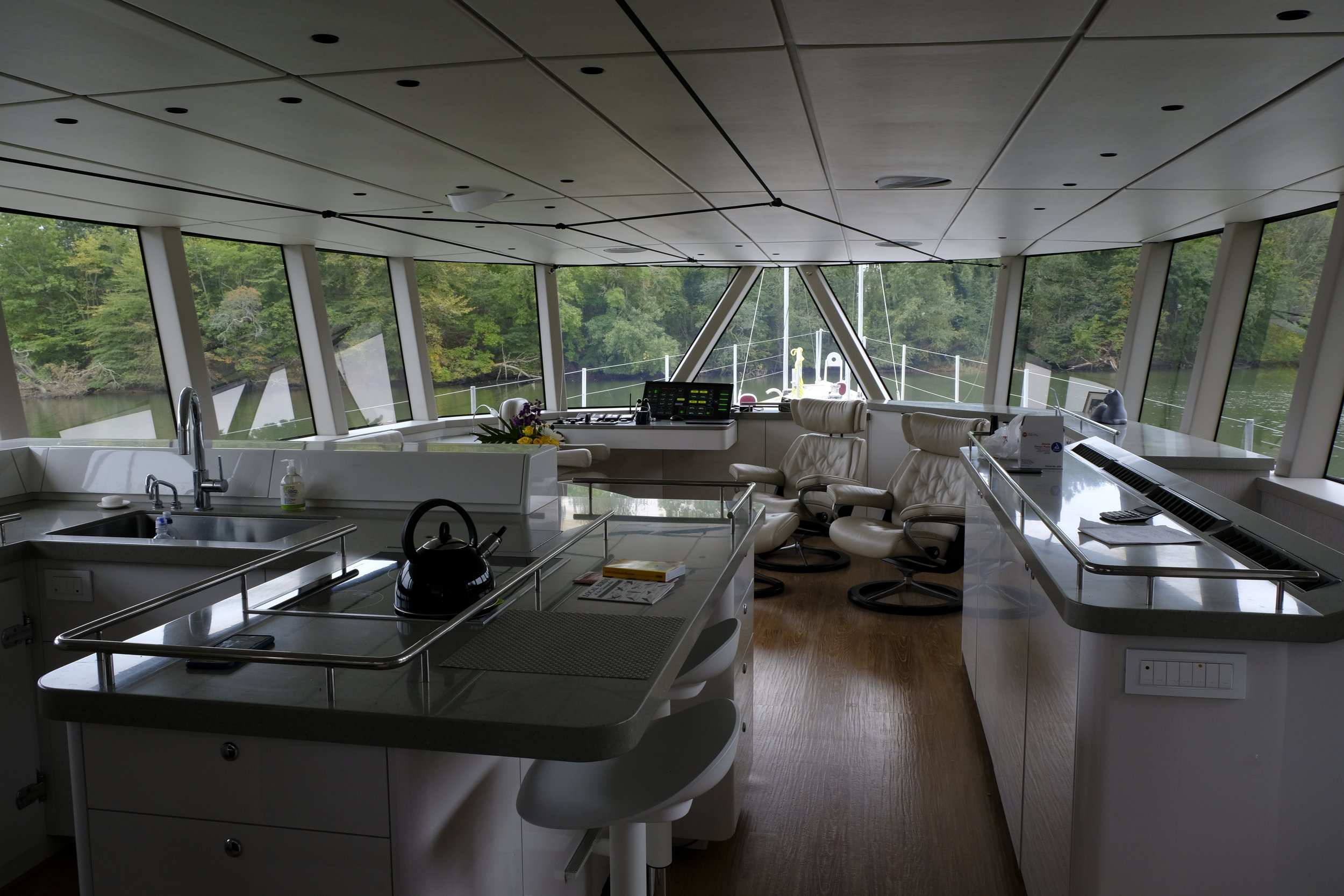 The gray saloon is minimalist and sophisticated. Everything is stored out of sight, yet readily accessible. Note the overhead spiderweb of Spectra line for holding on at sea. Motion is minimal at the center of this boat.