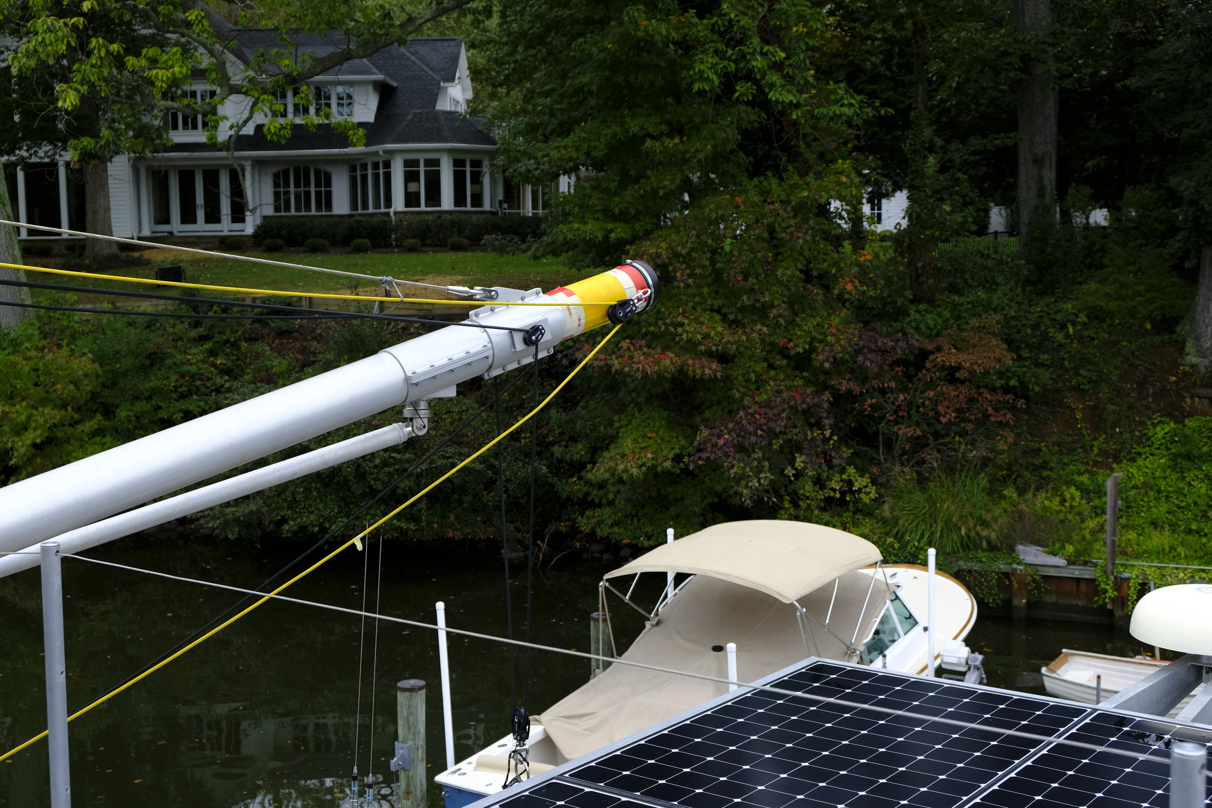 Details of the booms show the lines used to lift the dinghy and control the boom. All lines are super-strong Spectra lines, way stronger than their diameter might suggest. Note the solar array over the aft deck.
