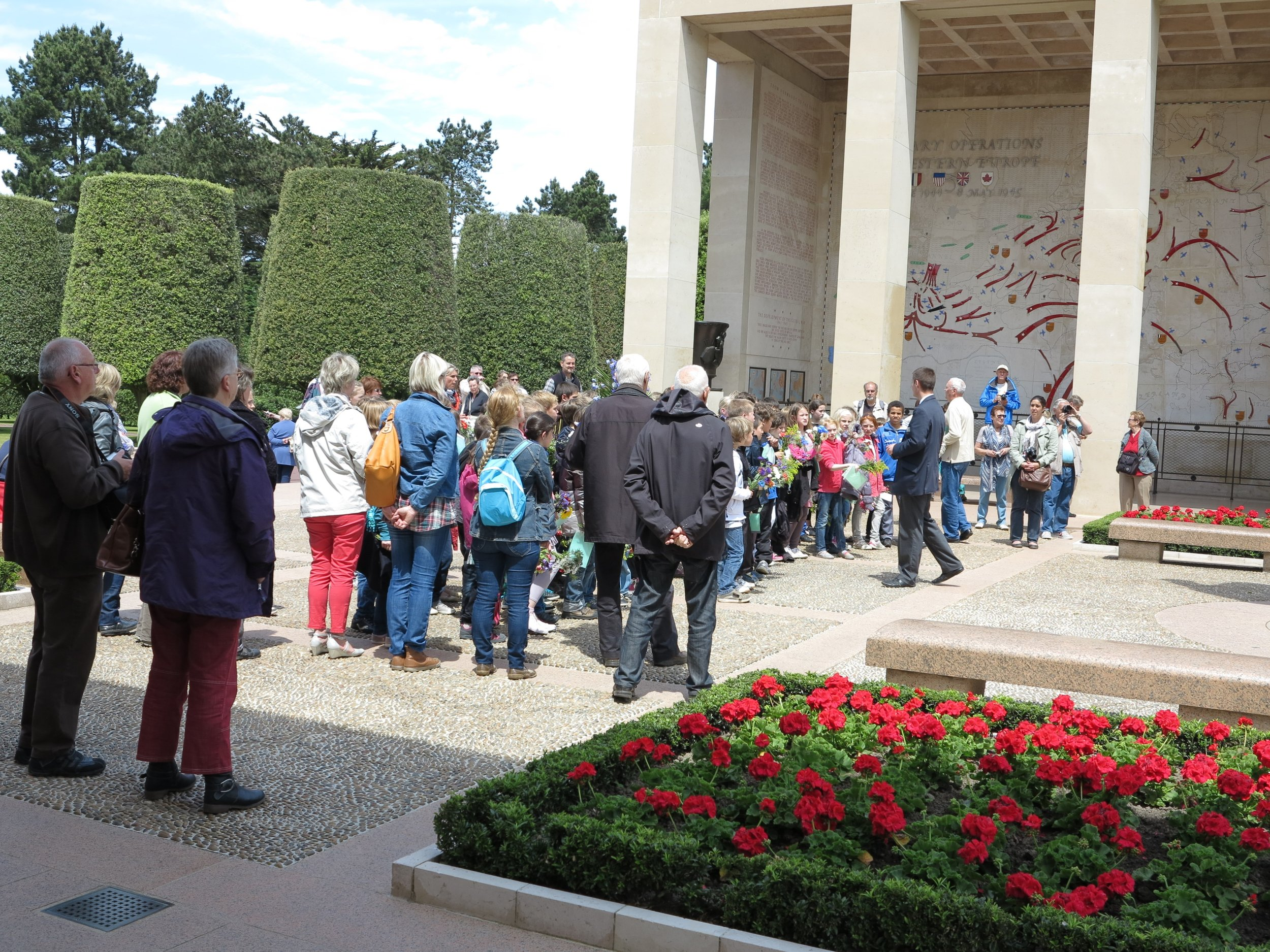 At the Normandy American Cemetery & Memorial, in Colleville-sur-Mer, France. Bus loads of French school children arrive at the memorial, with flowers and a paper with a specific grave location, to honor a soldier killed in the invasion of 1944. This brings this history up close and personal for these children, in an area of France that remains grateful for the sacrifice made by so many to free France from Nazi Germany.