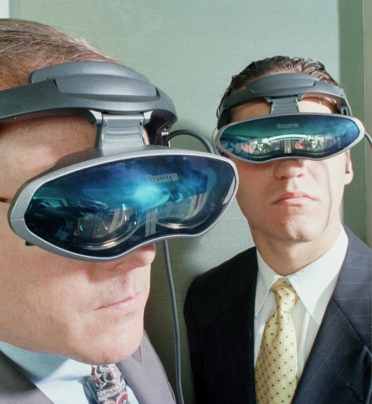 Getty Image: Sony executives Dan Nicholson, left, and Federico Stubbe show off the portable 10-ounce headset that connects to any analog or digital source in New York on July 29, 1998.