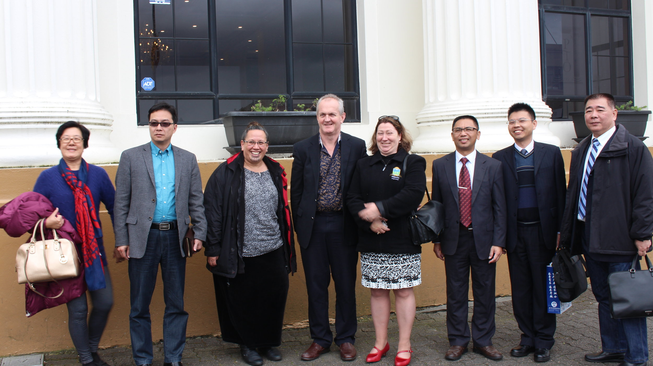 Mrs Wang and Fulong Wang, Learner Services Manager Maraea Cossey, FREEDOM Presidents Graeme and Susan Stevenson, Chao Lv, Wenlong Huang and Chunsong Huang outside their restored Public Trust Office with four of the Xiamen City University Presidents and a faculty member.