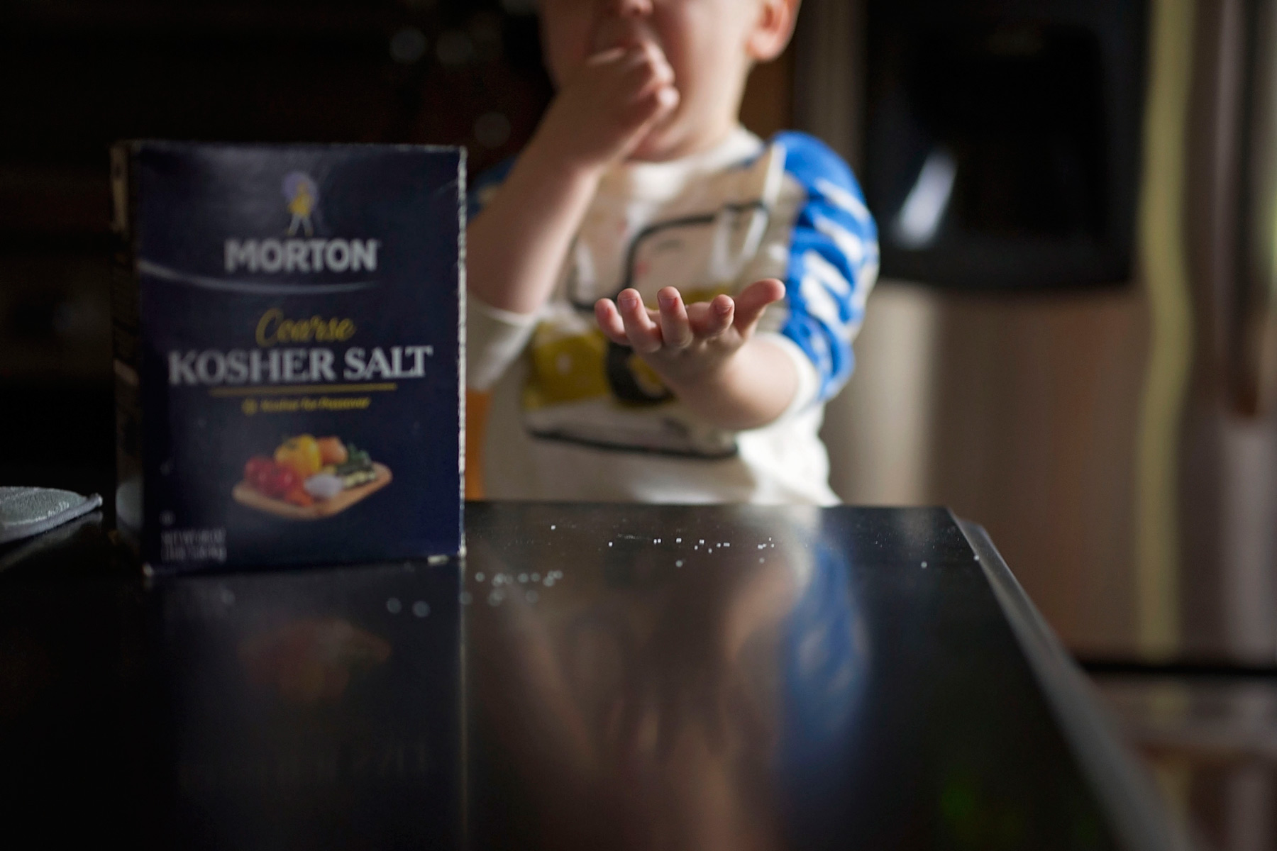 boy with hand outstretched eating salt
