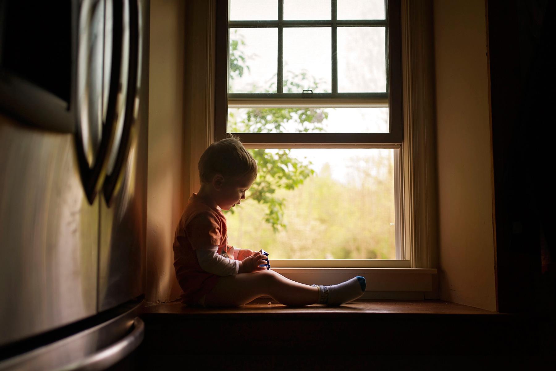 little boy having a snack on windowsill