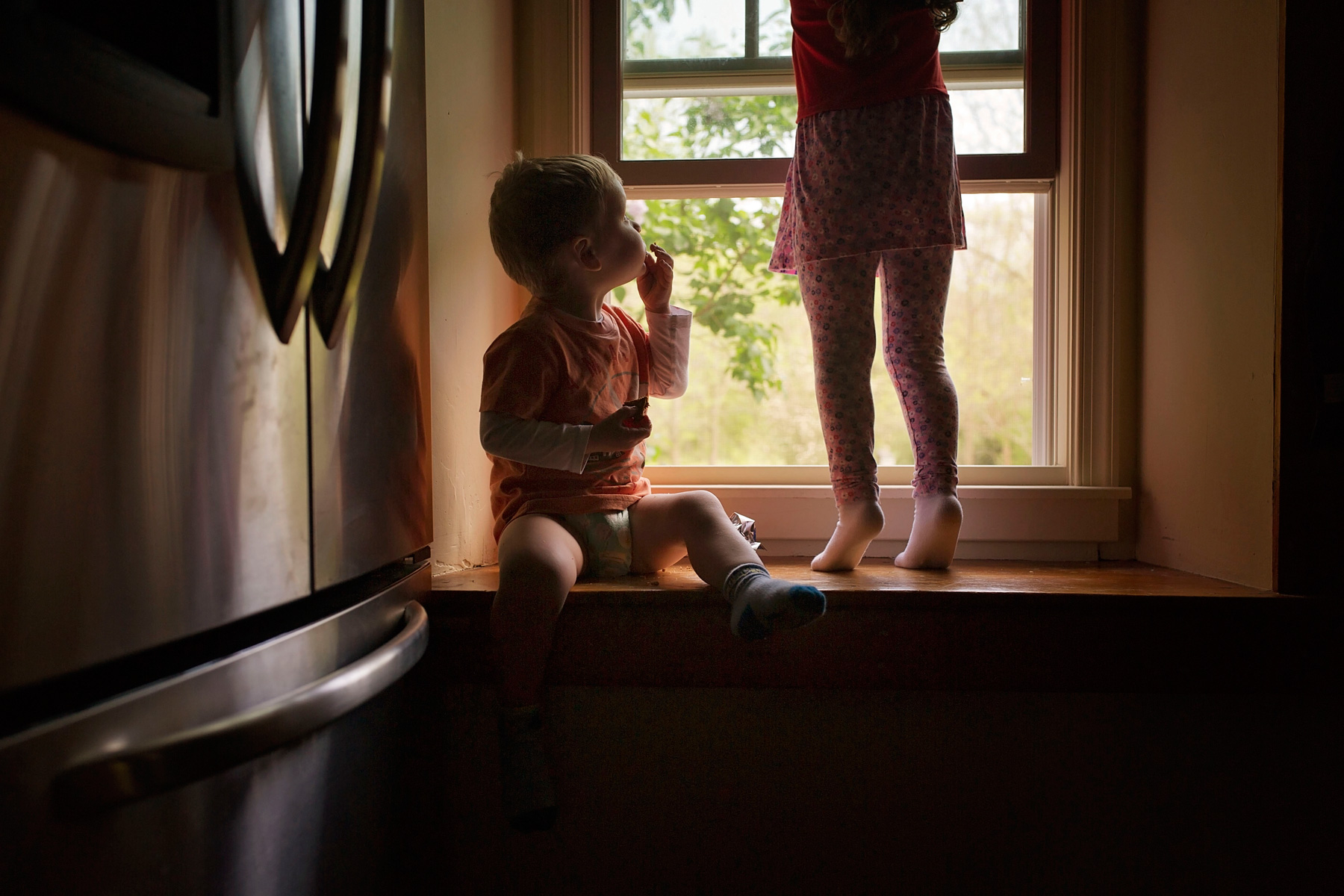 little girl closes window while little brother looks up at her