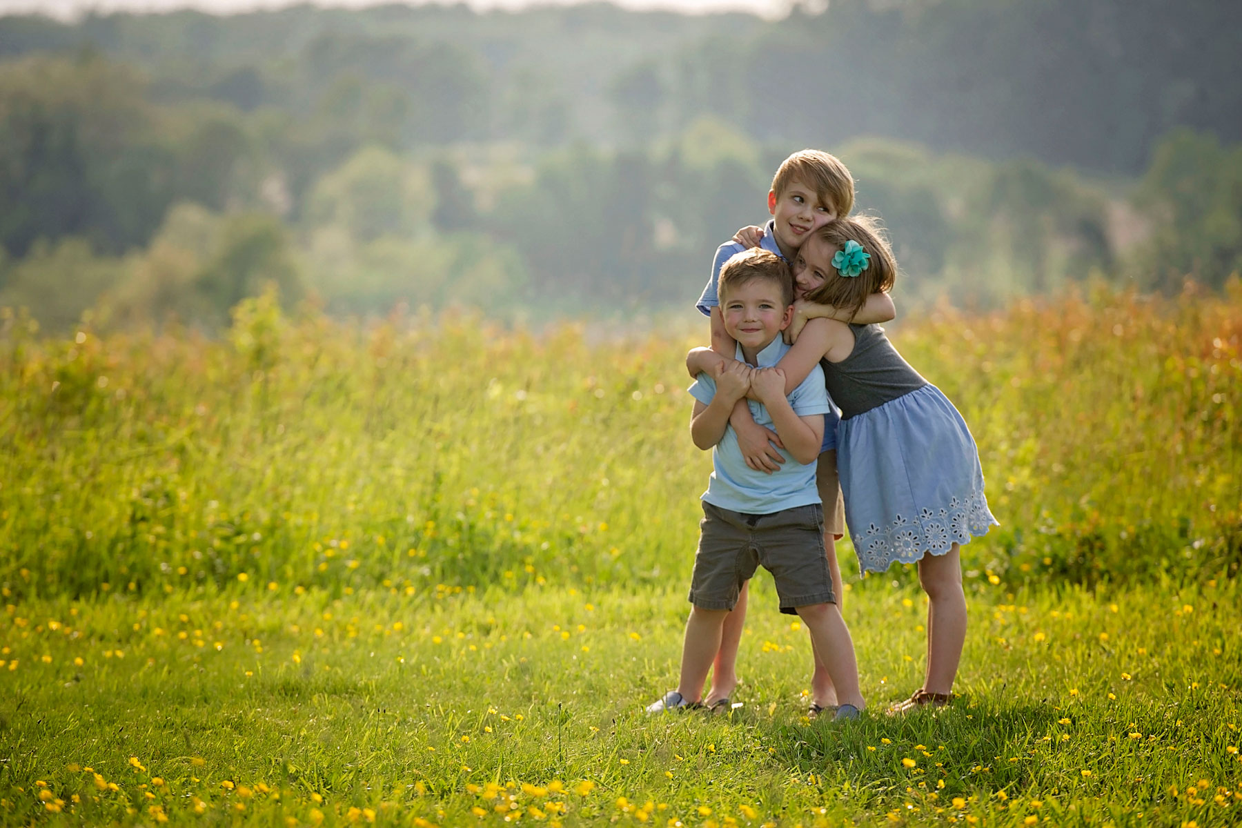 three siblings, one girl, in a big bear hug