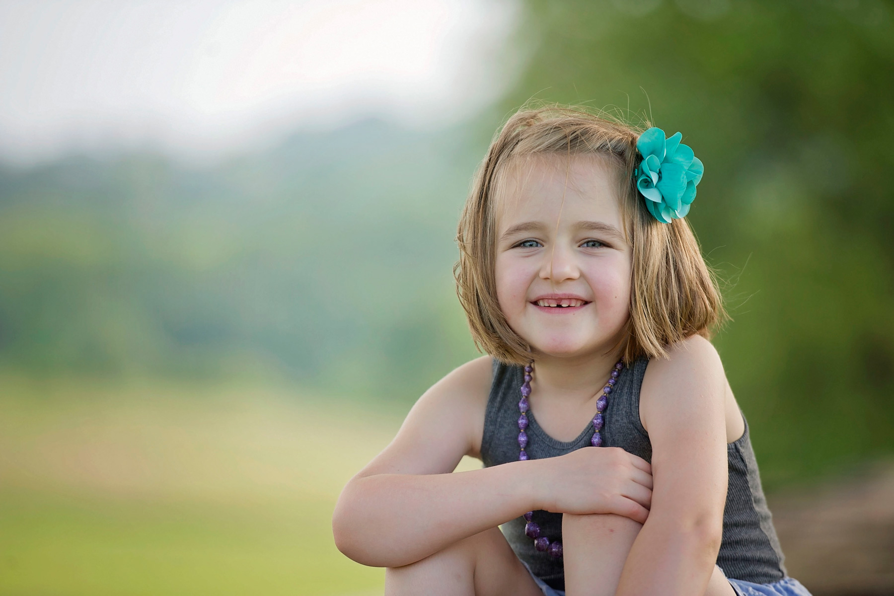 little girl smiling with arm across her knees