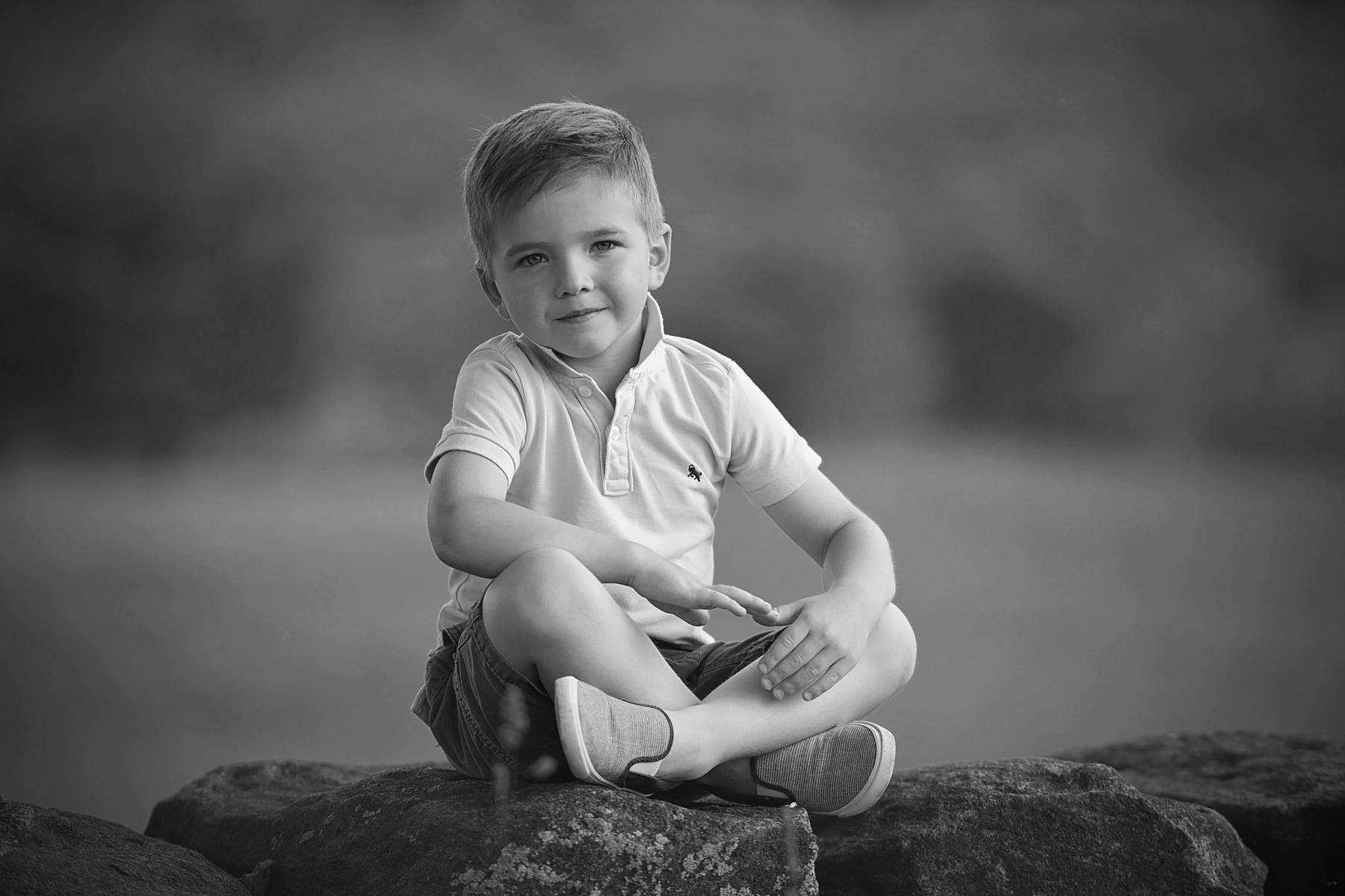 four year old sitting cross legged on rocks