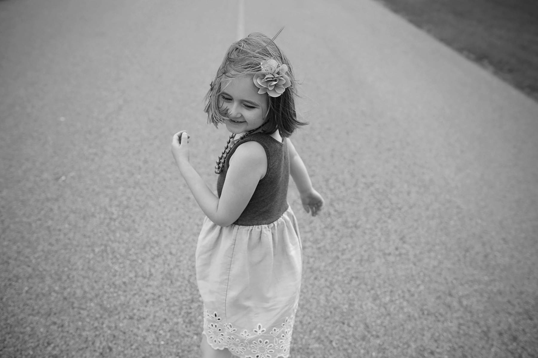 little girl turned back looking over shoulder while walking down the road