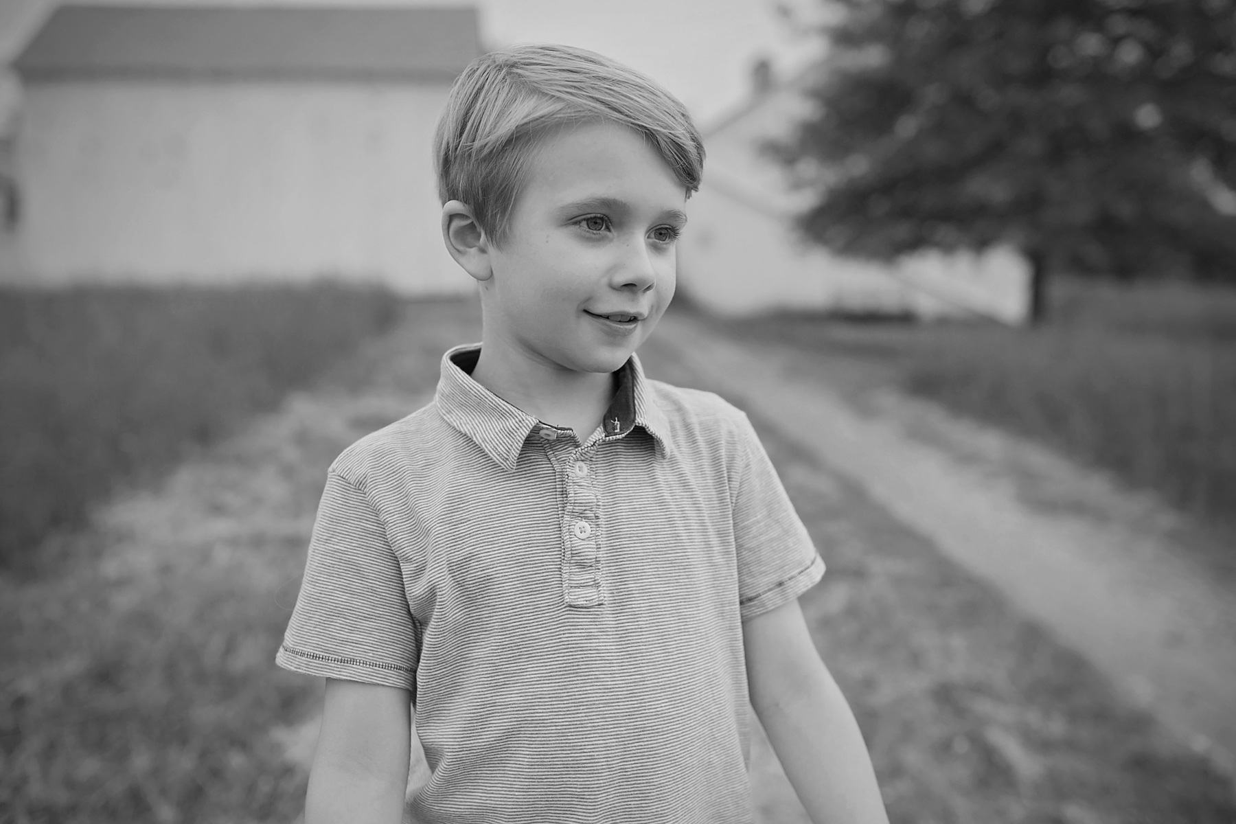 black and white of nine year old boy standing outside