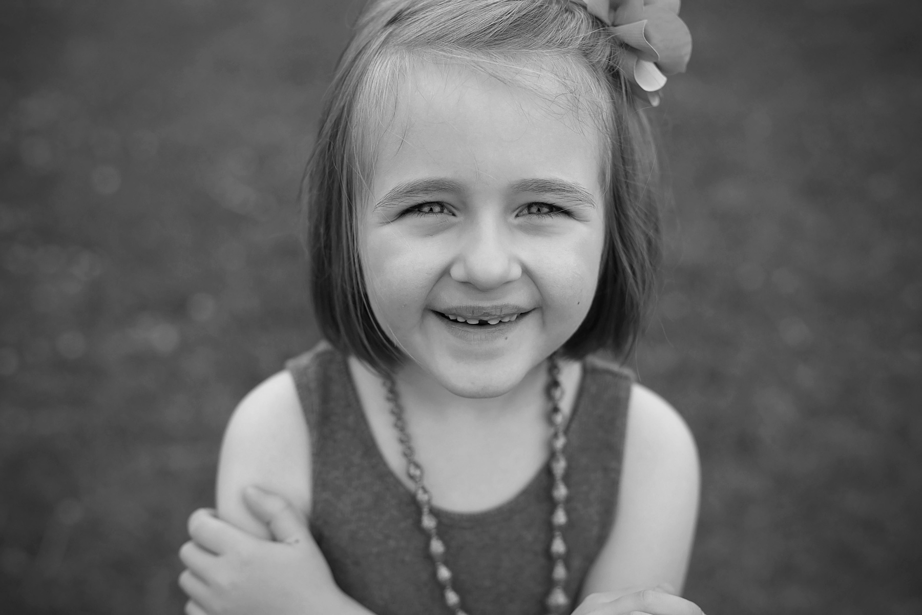 black and white of young girl smiling with arms crossed