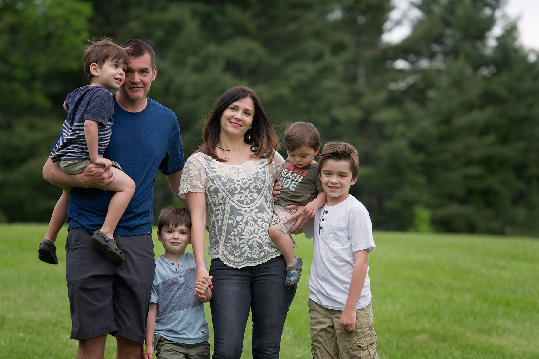 Mother, father and four young boys pose for picture