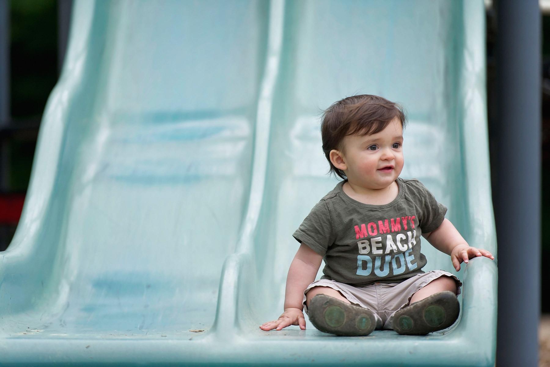 little boy sits at the bottom or slide smiling