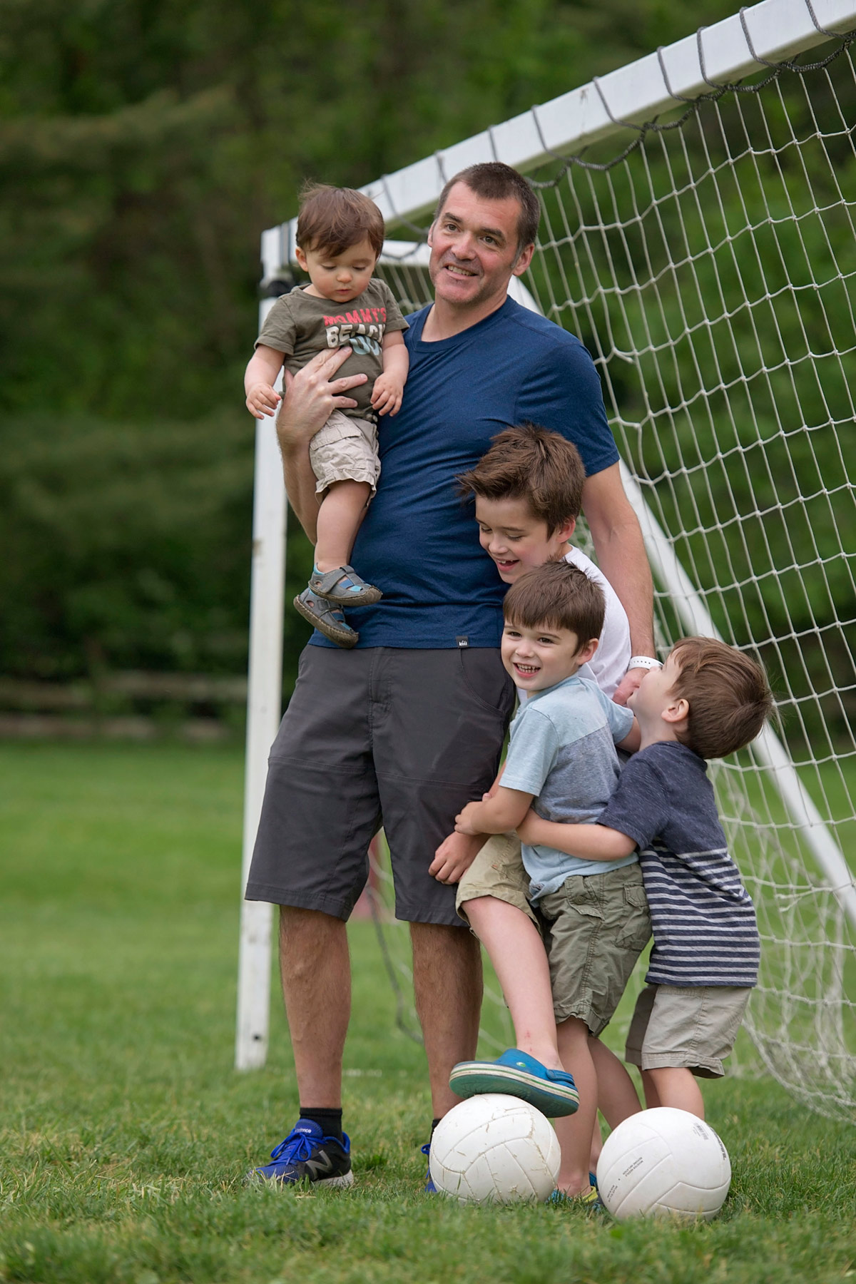 father with four sons in soccer goal hugging