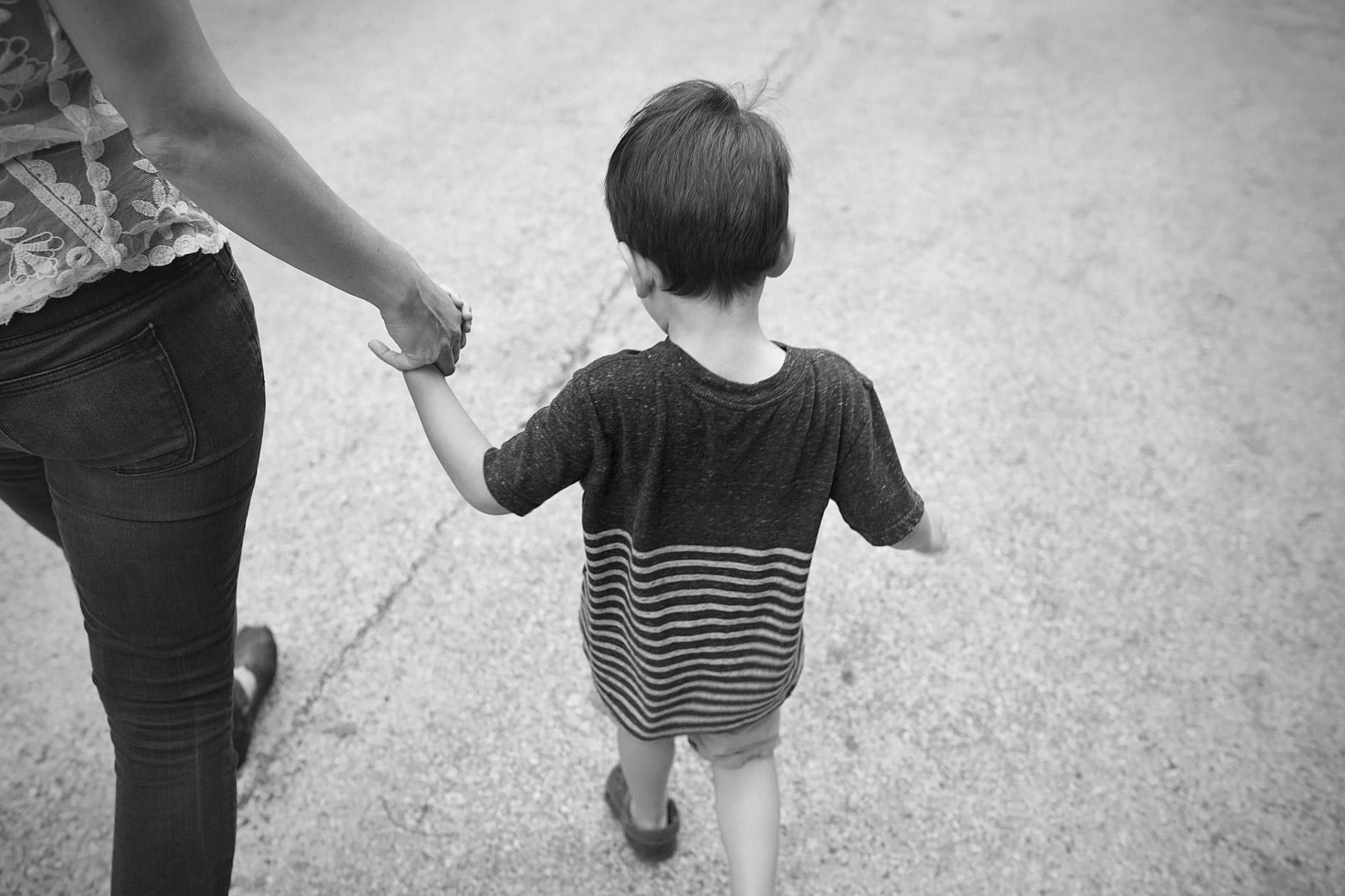 boy walks away from camera holding mom's hand