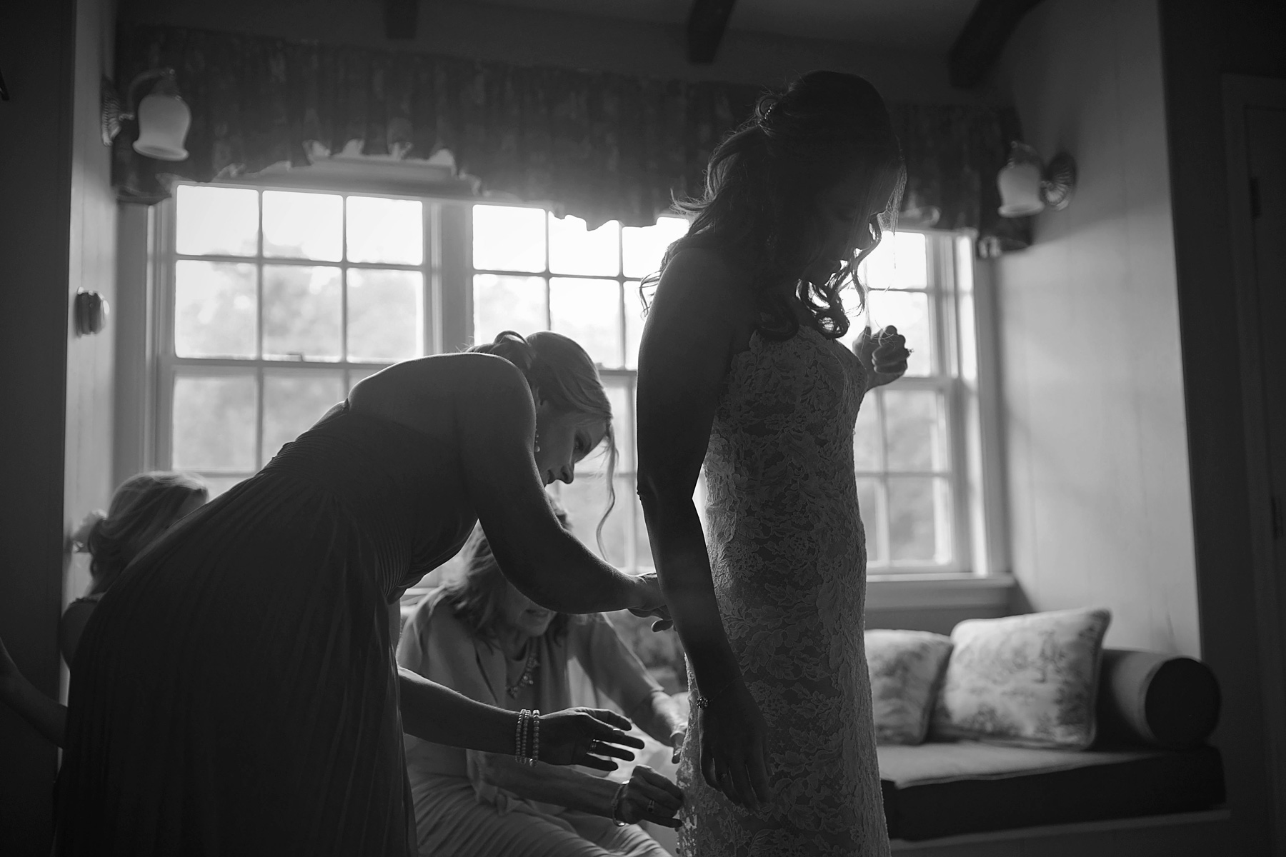 Backlit image of bride getting dressed while mother helps.