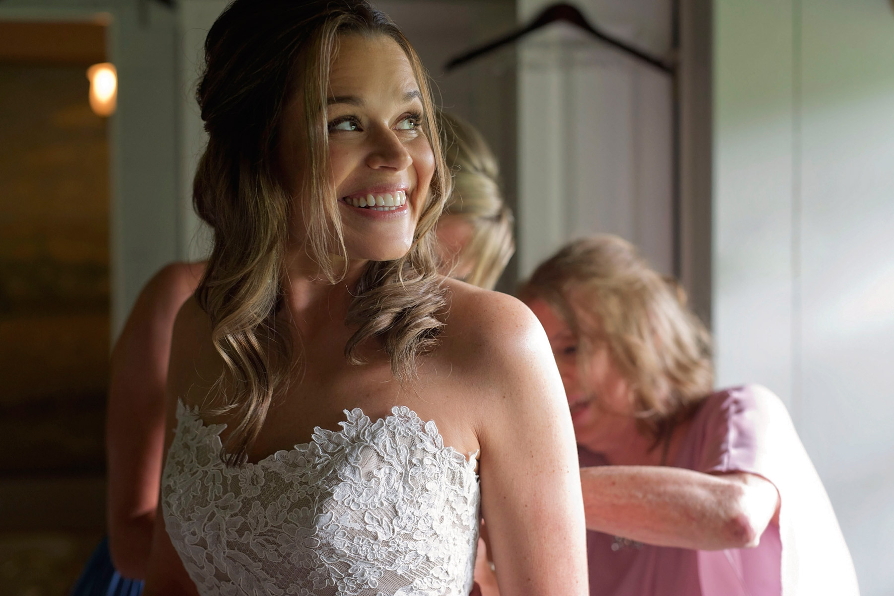 Bride looking excited while getting into her wedding gown
