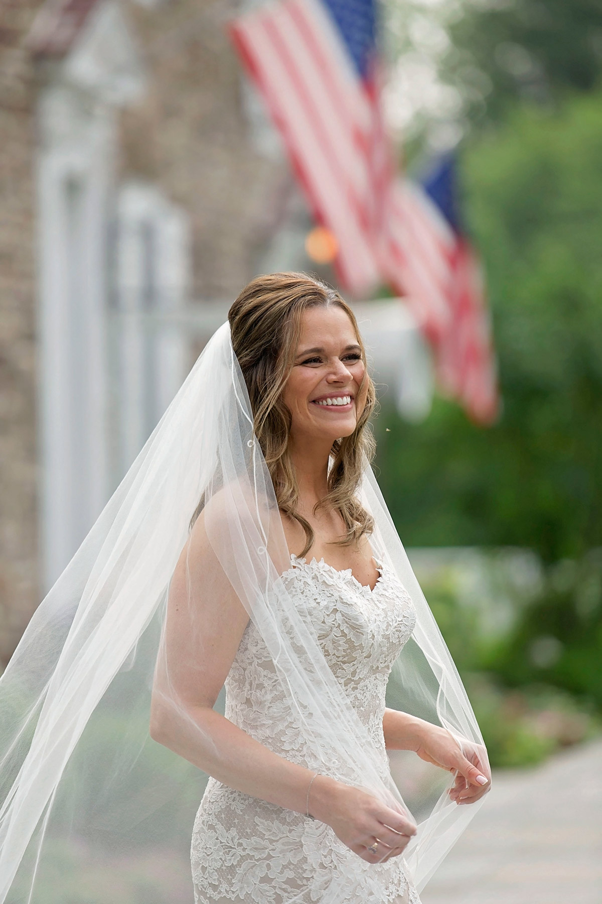 Bride holds onto veil while smiling in front of the Woolverton Inn in Stockton