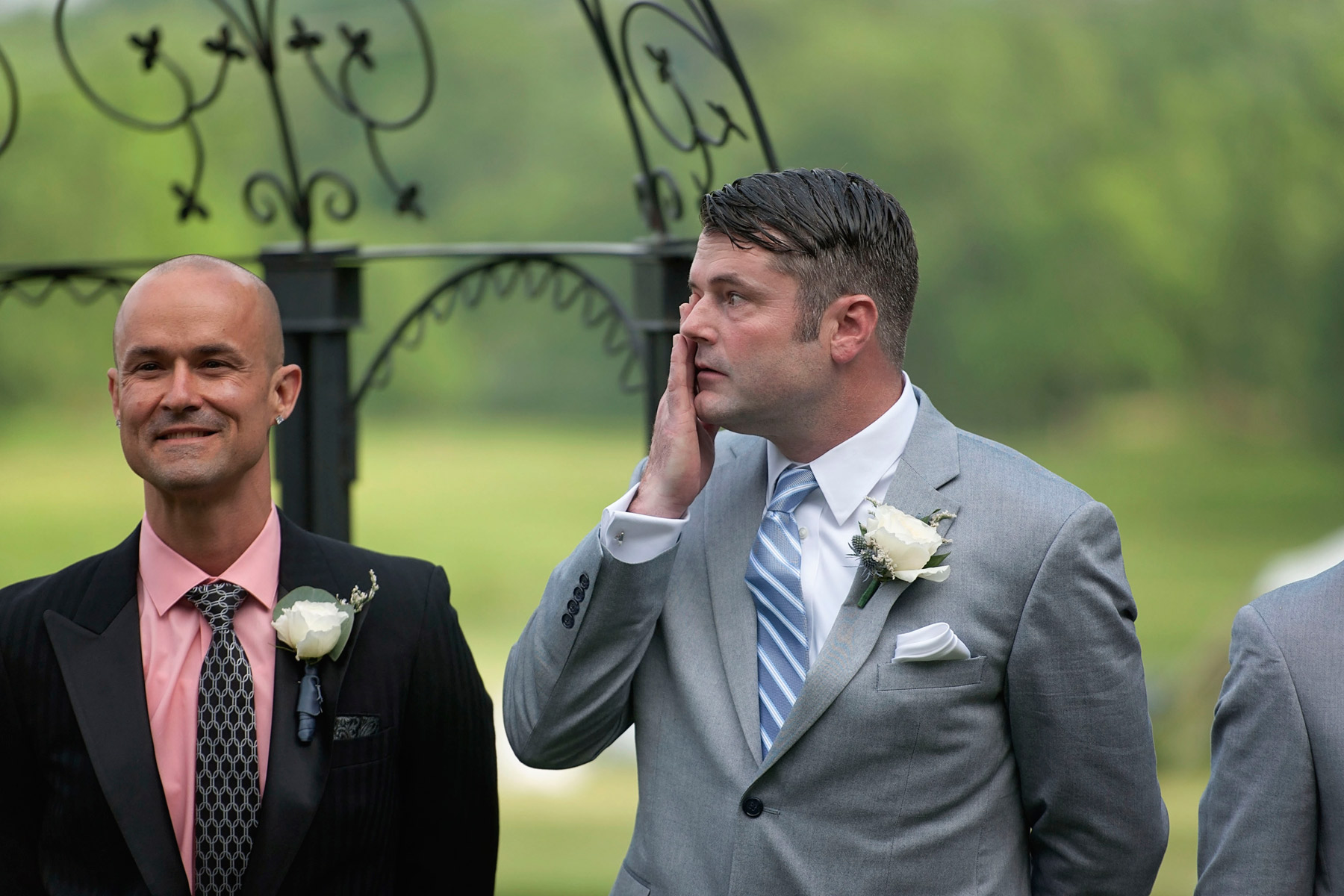 Groom wipes a tear as he sees his bride coming down the aisle