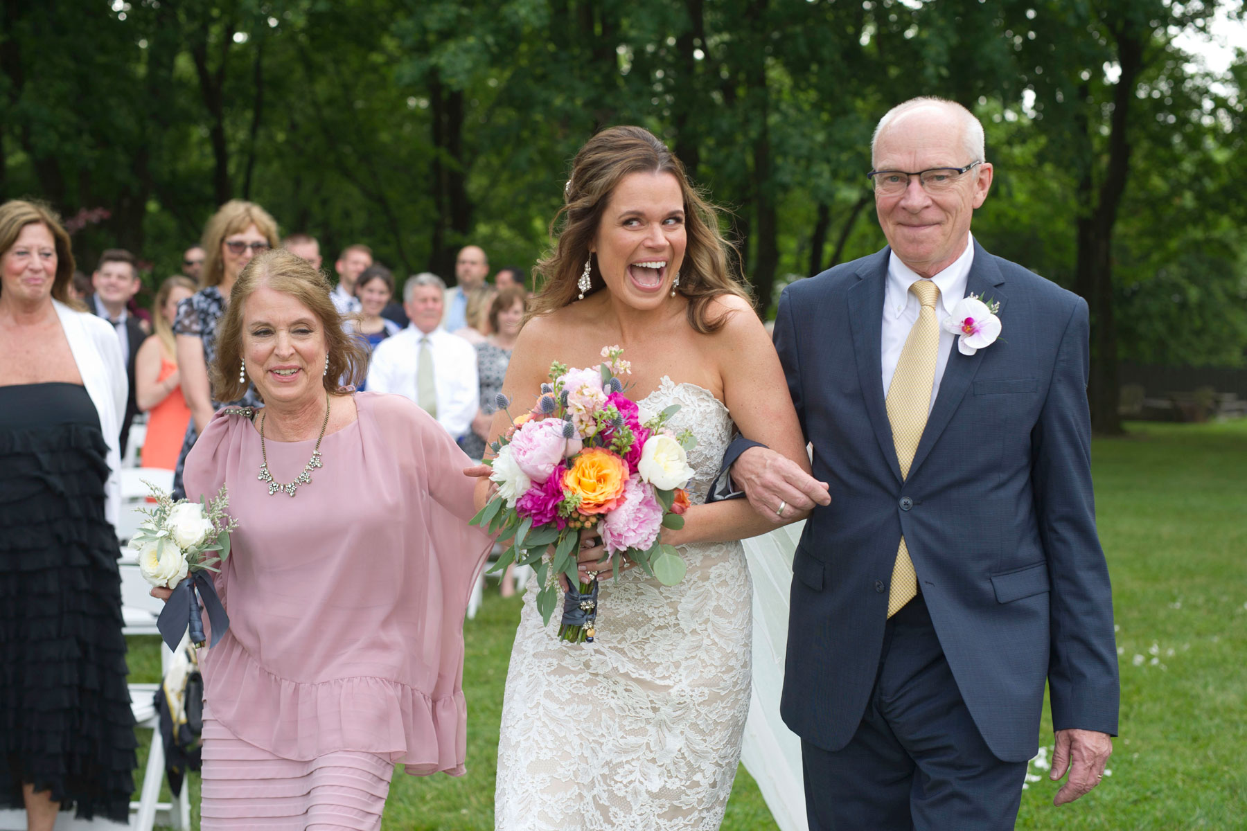 Bride gives her groom an excited look as she reaches the front of the aisle