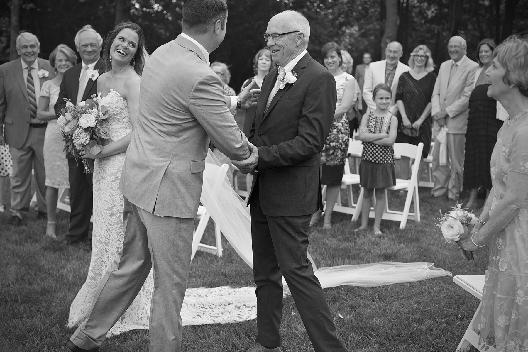 Father of the bride shakes grooms hand as bride looks on