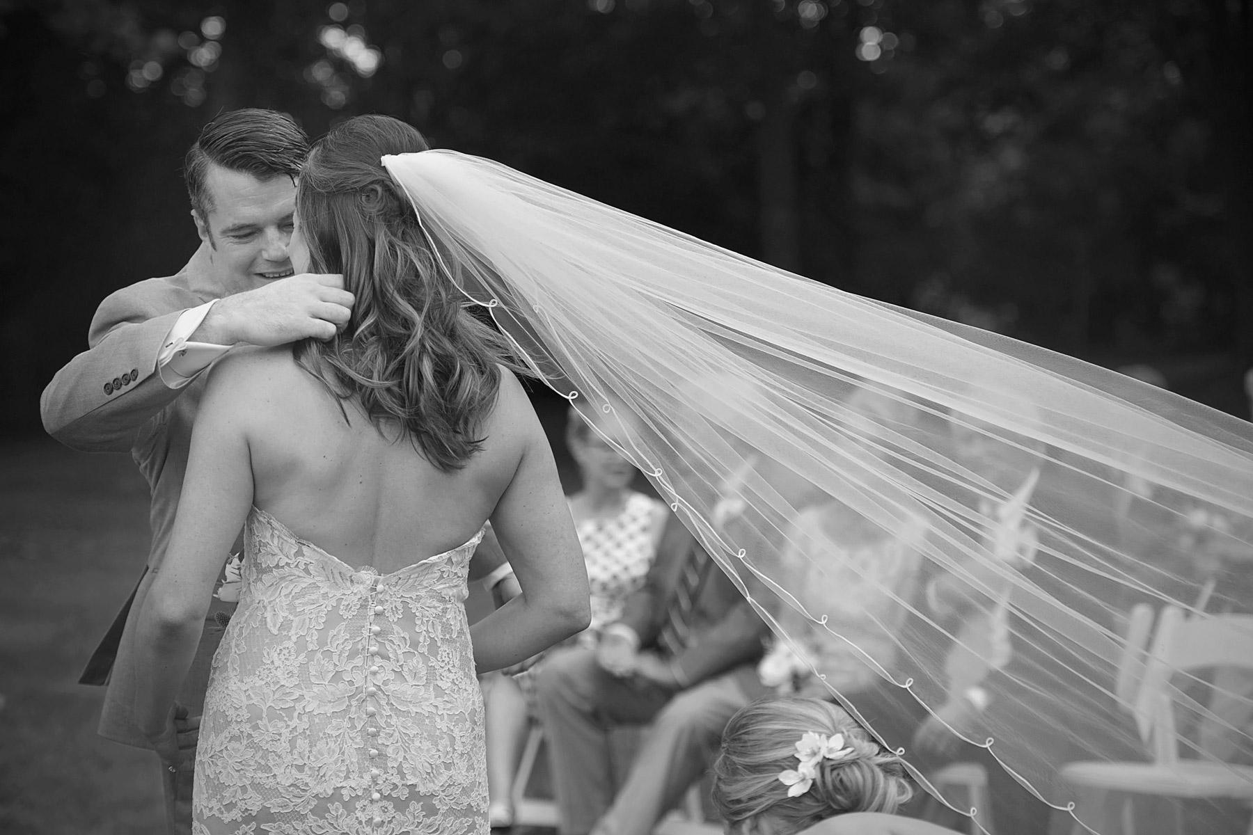 groom tucks hair behind bride's ear as her veil blows in the wind