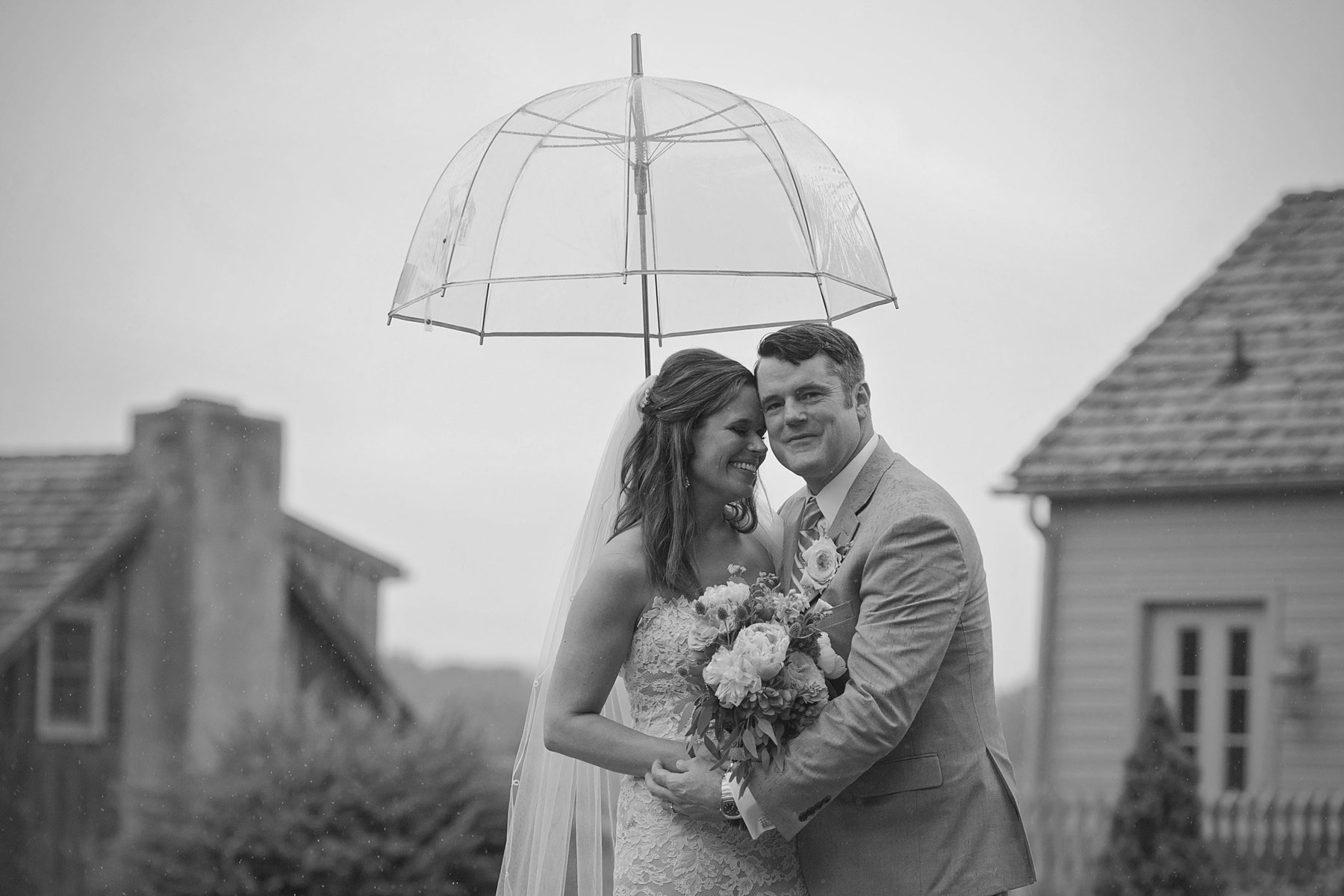 Bride and groom embrace under clear umbrella
