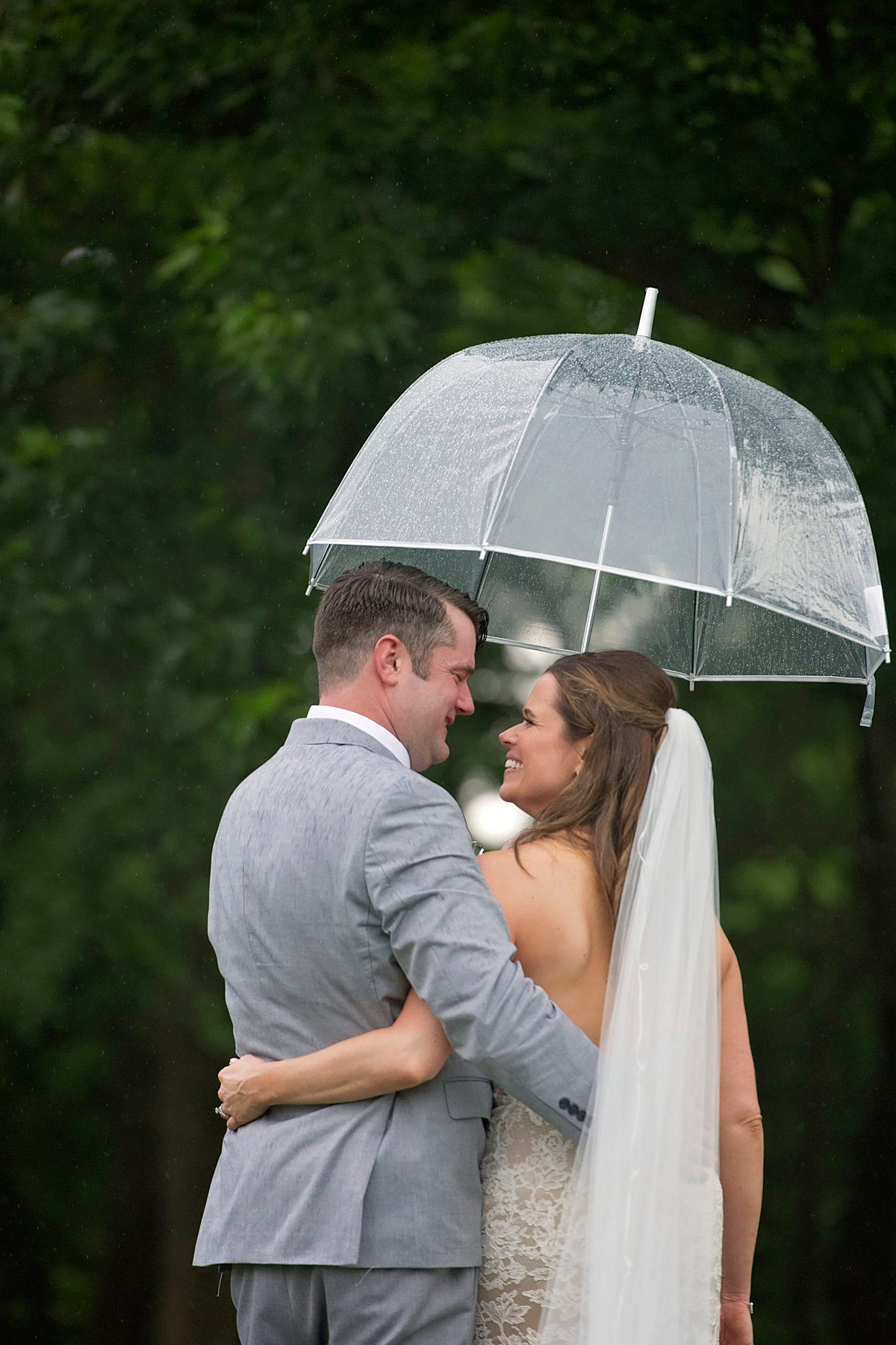 bride and groom walk away from camera under clear umbrella, looking at one another