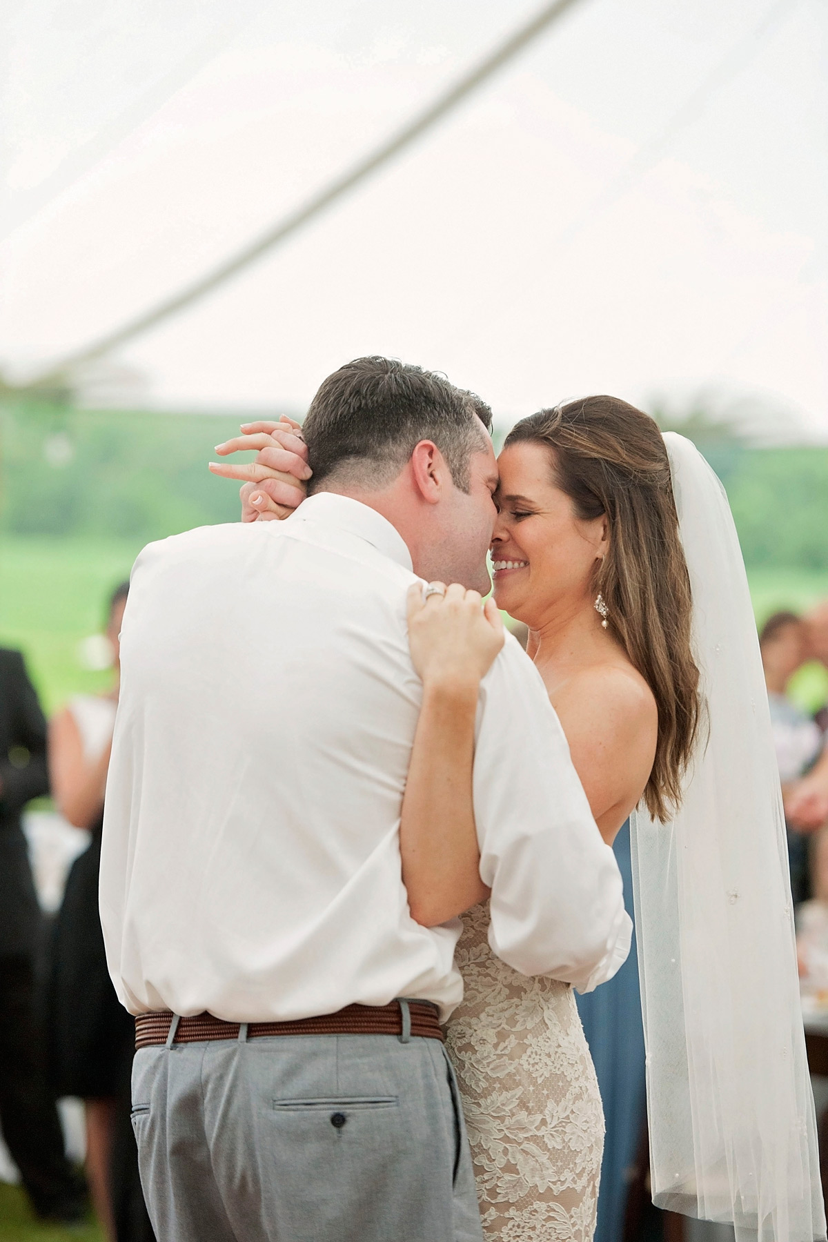 bride and groom share first dance under a tent