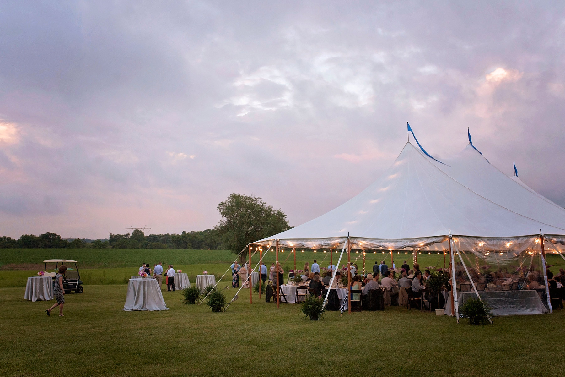 Sailcloth tent with twinkle lights and a pink sunset