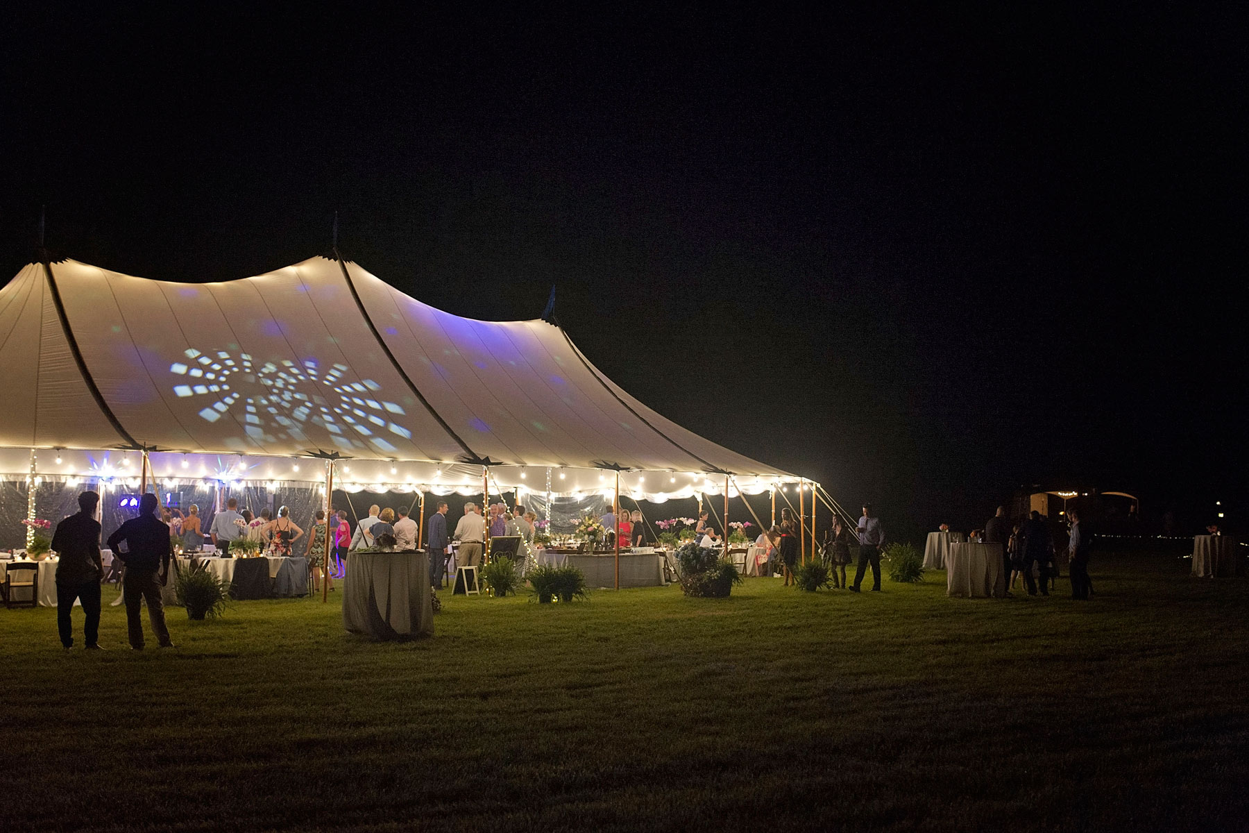 Sailcloth tent lit at night against a dark sky