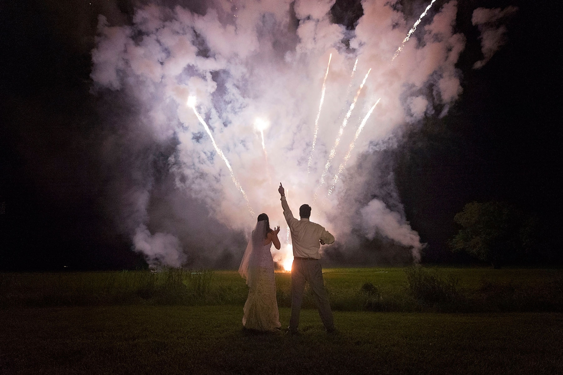 Bride and groom react to fireworks with excitement