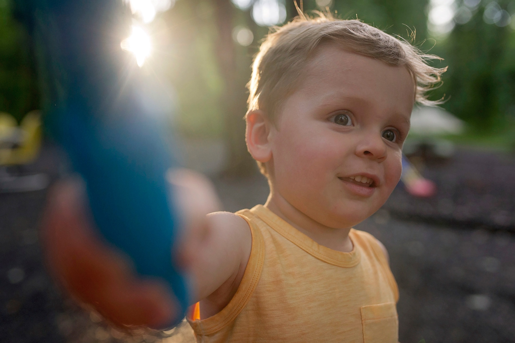 toddler boy holding blue object backlit by the sun