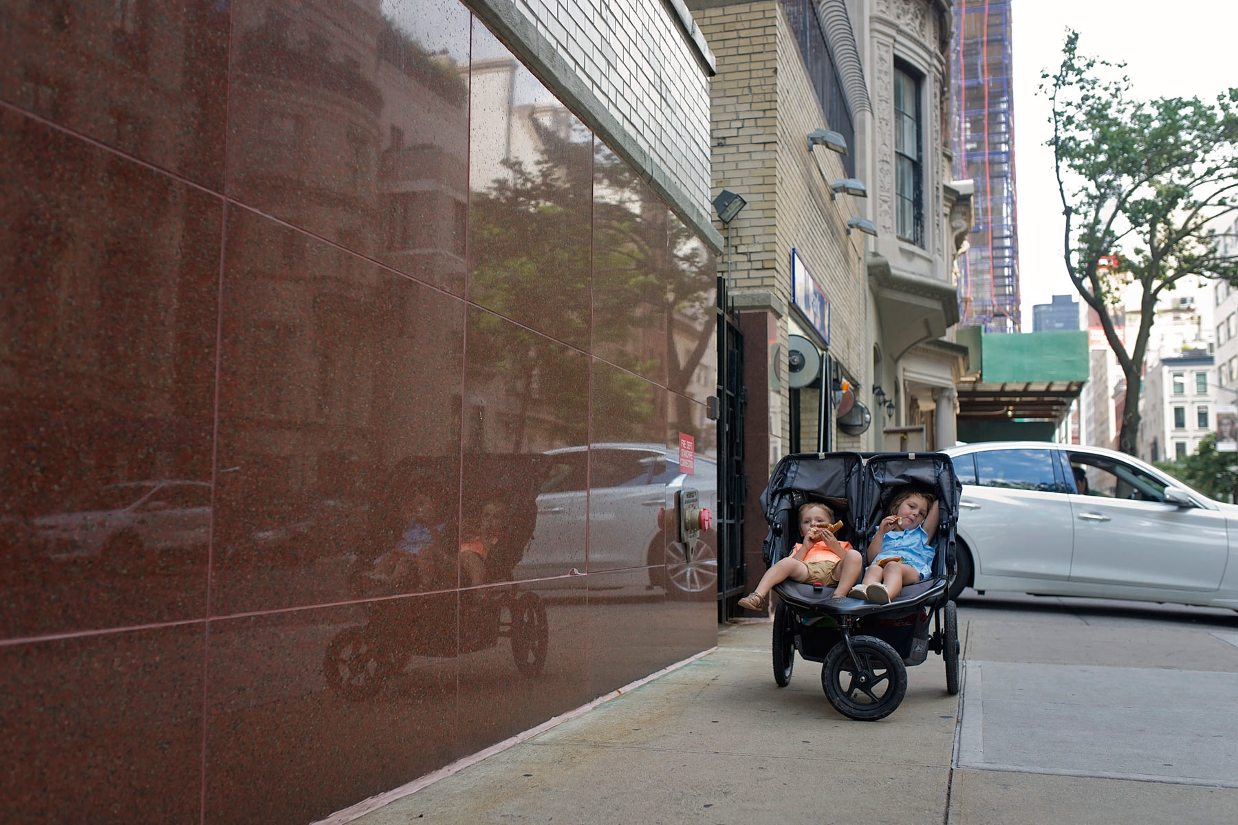 boy and girl sitting in double stroller eating a soft pretzel in NYC