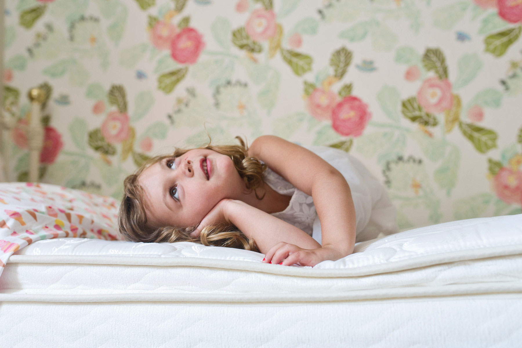3 year old lays on bed daydreaming and looking at ceiling