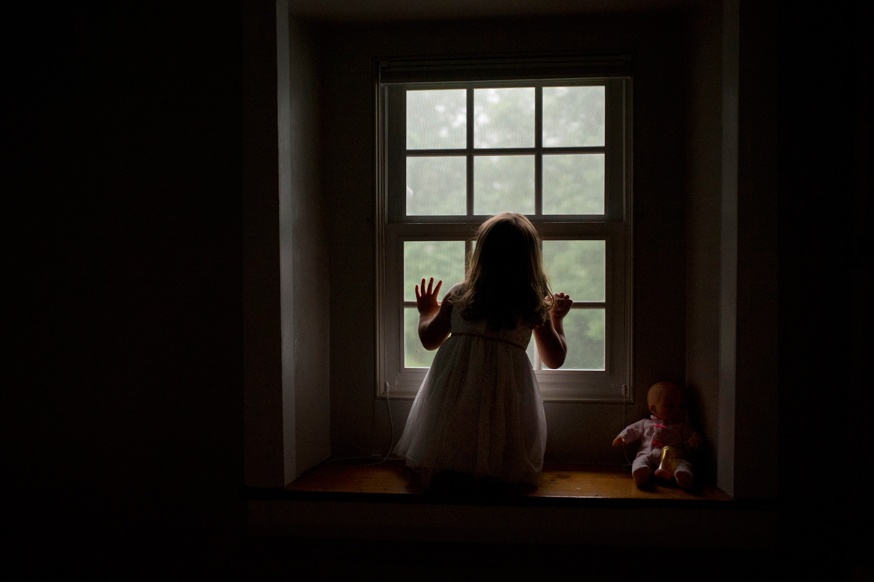 girl kneels at window observing the fog