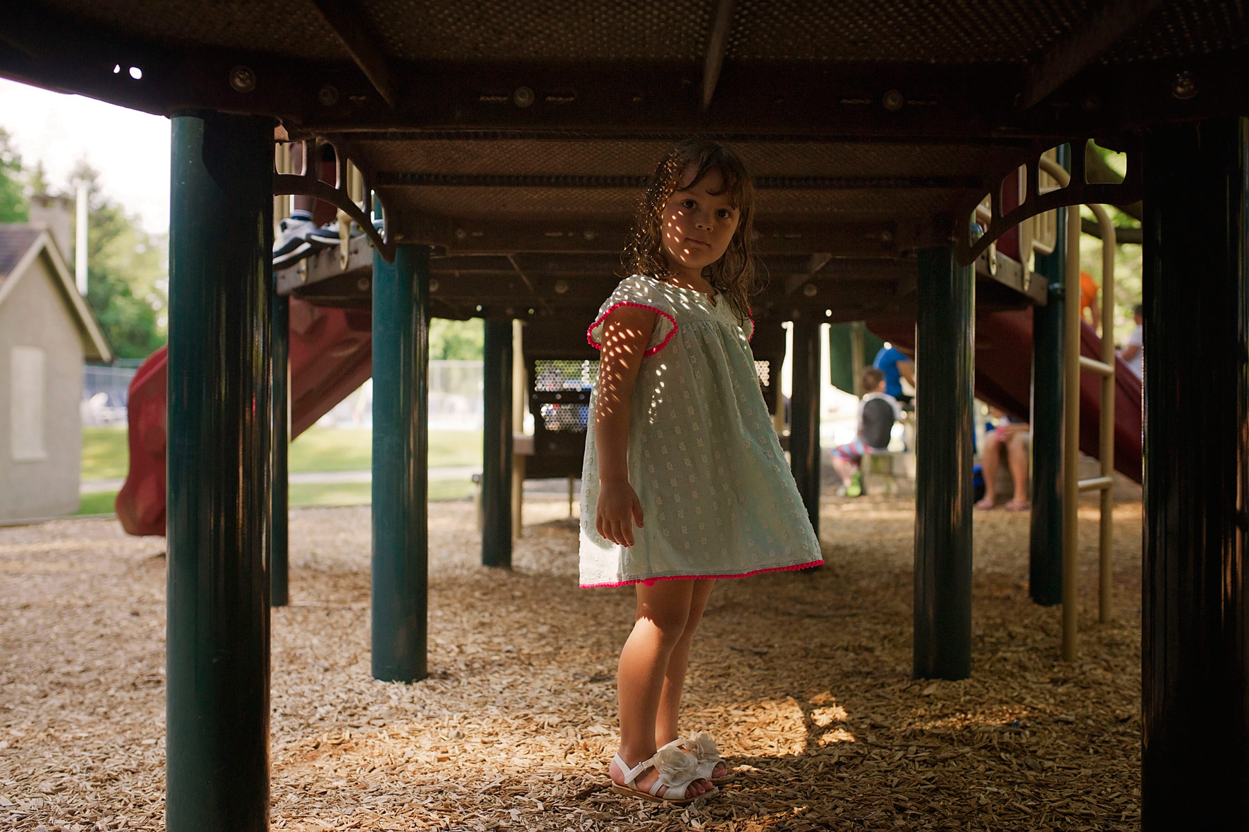 4 year old stands underneath playground while light creates a patter on her dress and face