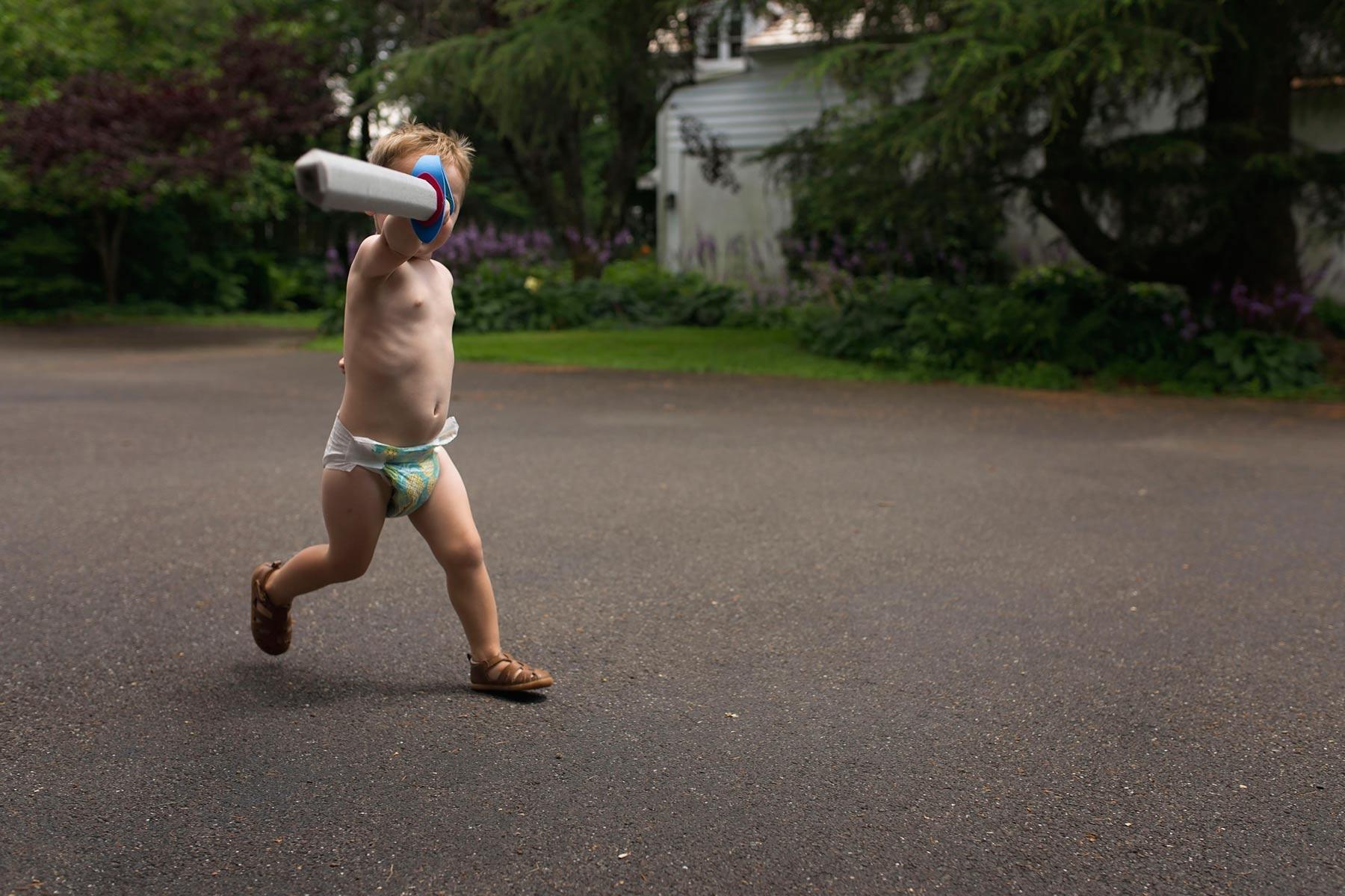 Little boy runs towards camera yielding a sword while wearing a diaper