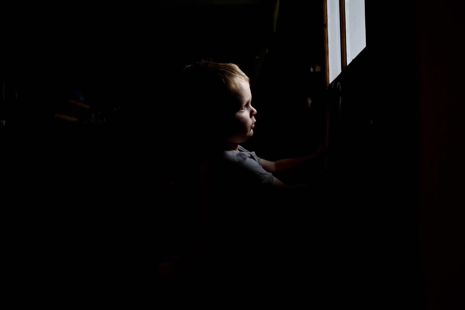 little boy's face lit by morning light through the window while the rest of the room is in shadows